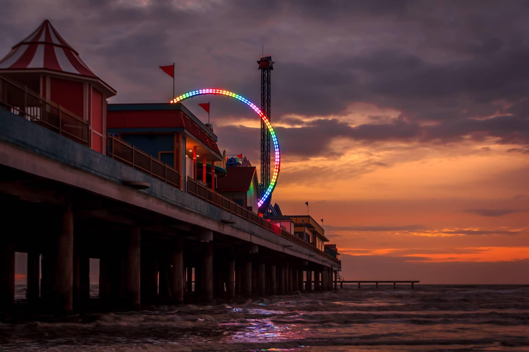 The rainbow-colored lights of a thrill ride on Galveston, Texas' Pleasure Pier pierce the dawn's twilight.