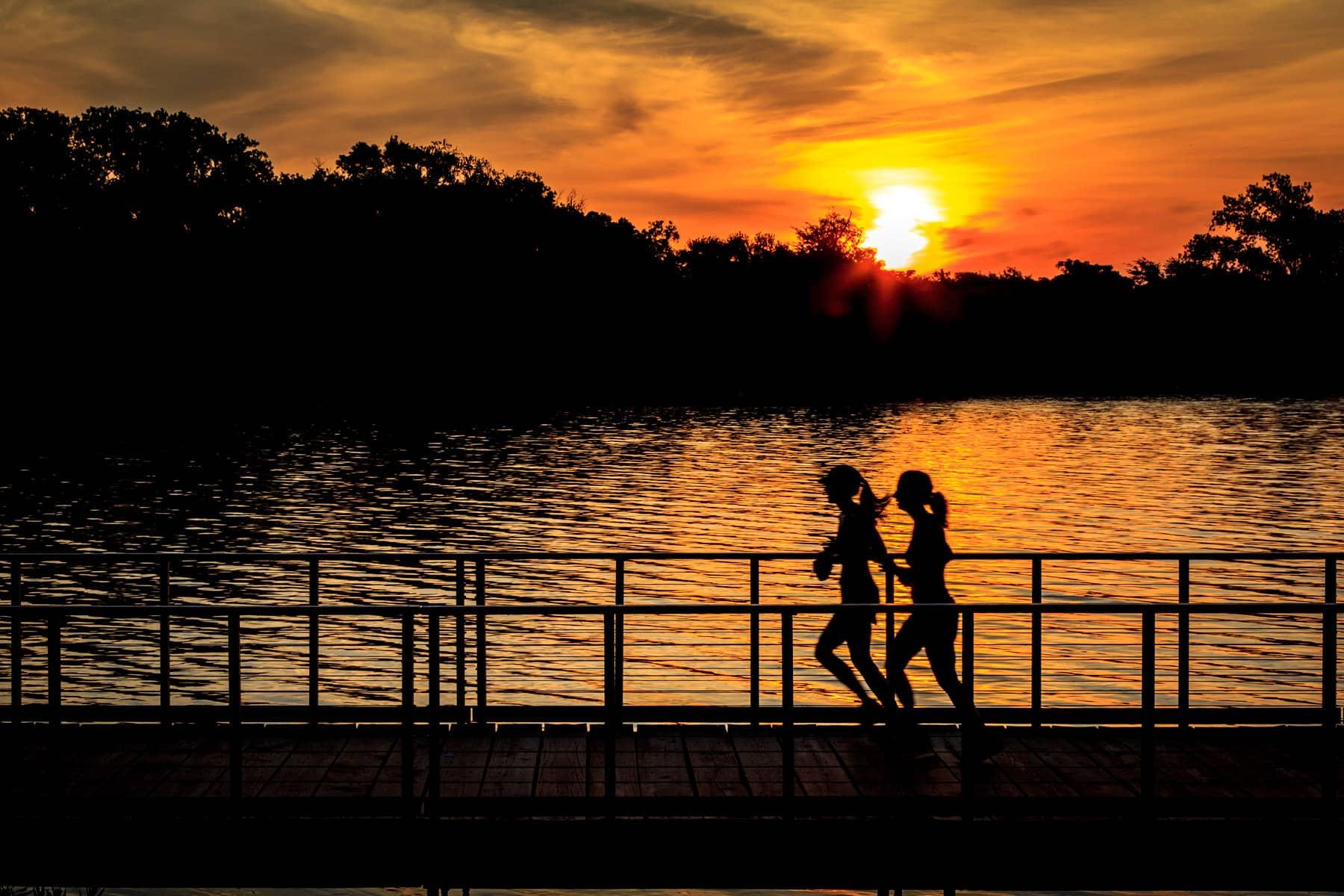 Joggers run along a footbridge as the sun rises over White Rock Lake, Dallas.