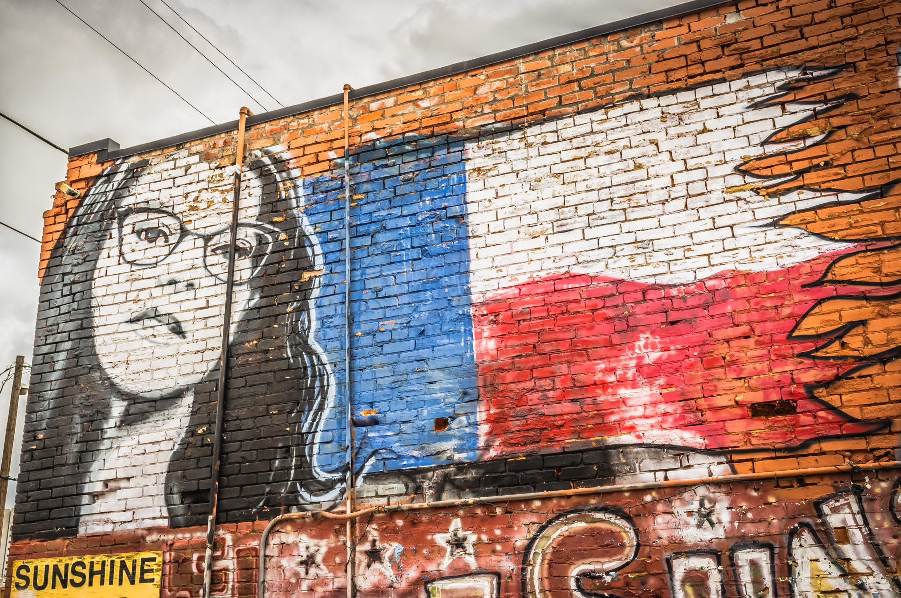 A mural of singer-songwriter Lisa Loeb and a stylized Texas flag, found in Dallas' Deep Ellum neighborhood.