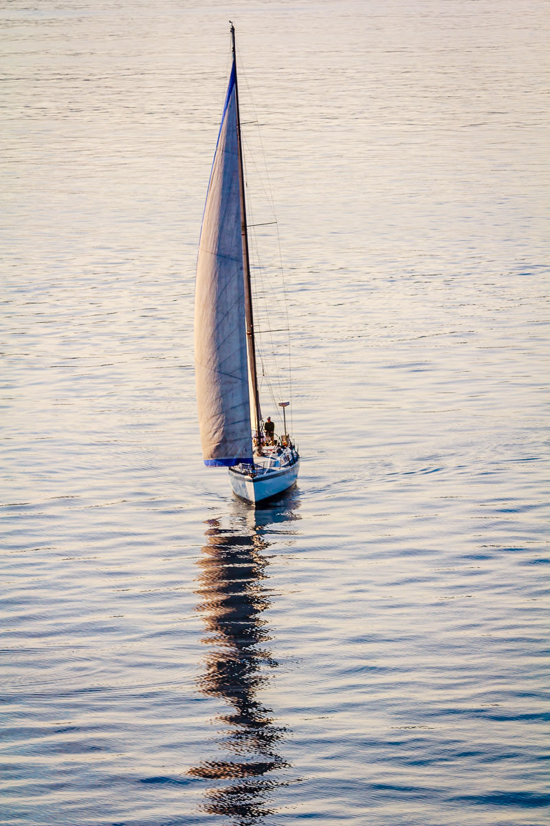 A sailboat navigates the smooth waters of Puget Sound just north of Seattle.