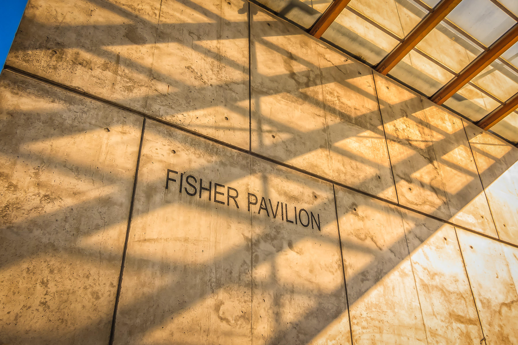 The morning sun throws shadows over the engraved name of the Fisher Pavilion at the Seattle Center.