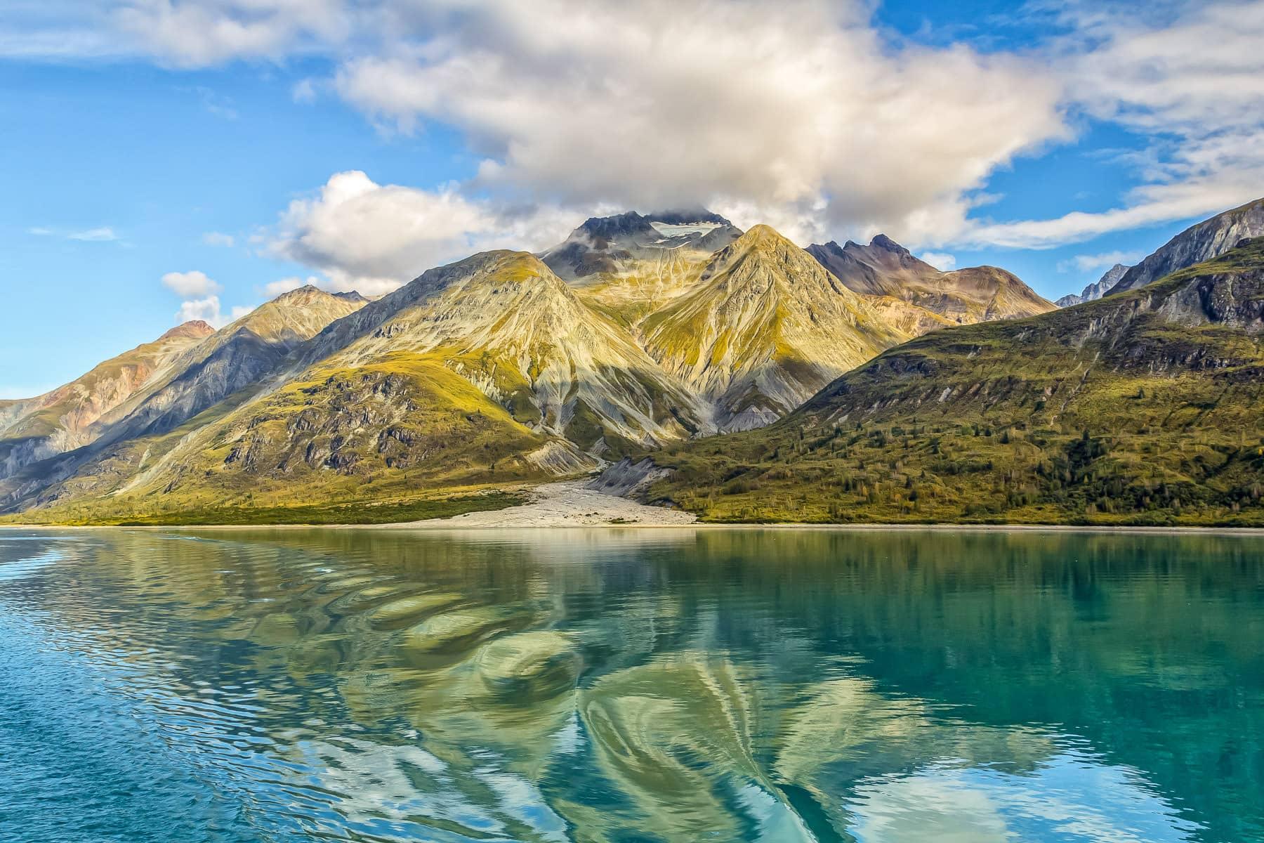 A cloud envelops a small, glacier-topped mountain in Alaska's Glacier Bay National Park.