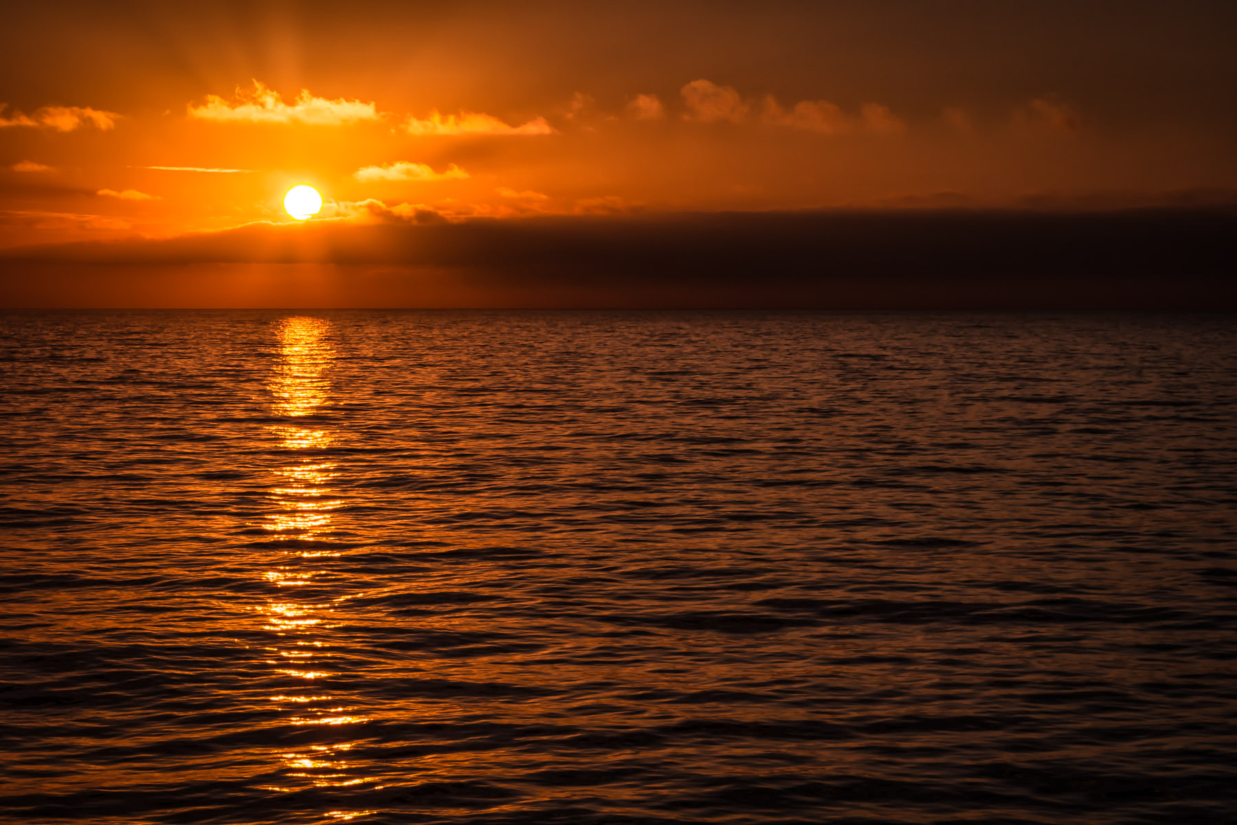 The sun sets on the Hecate Strait off the coast of the Queen Charlotte Islands, British Columbia, Canada.