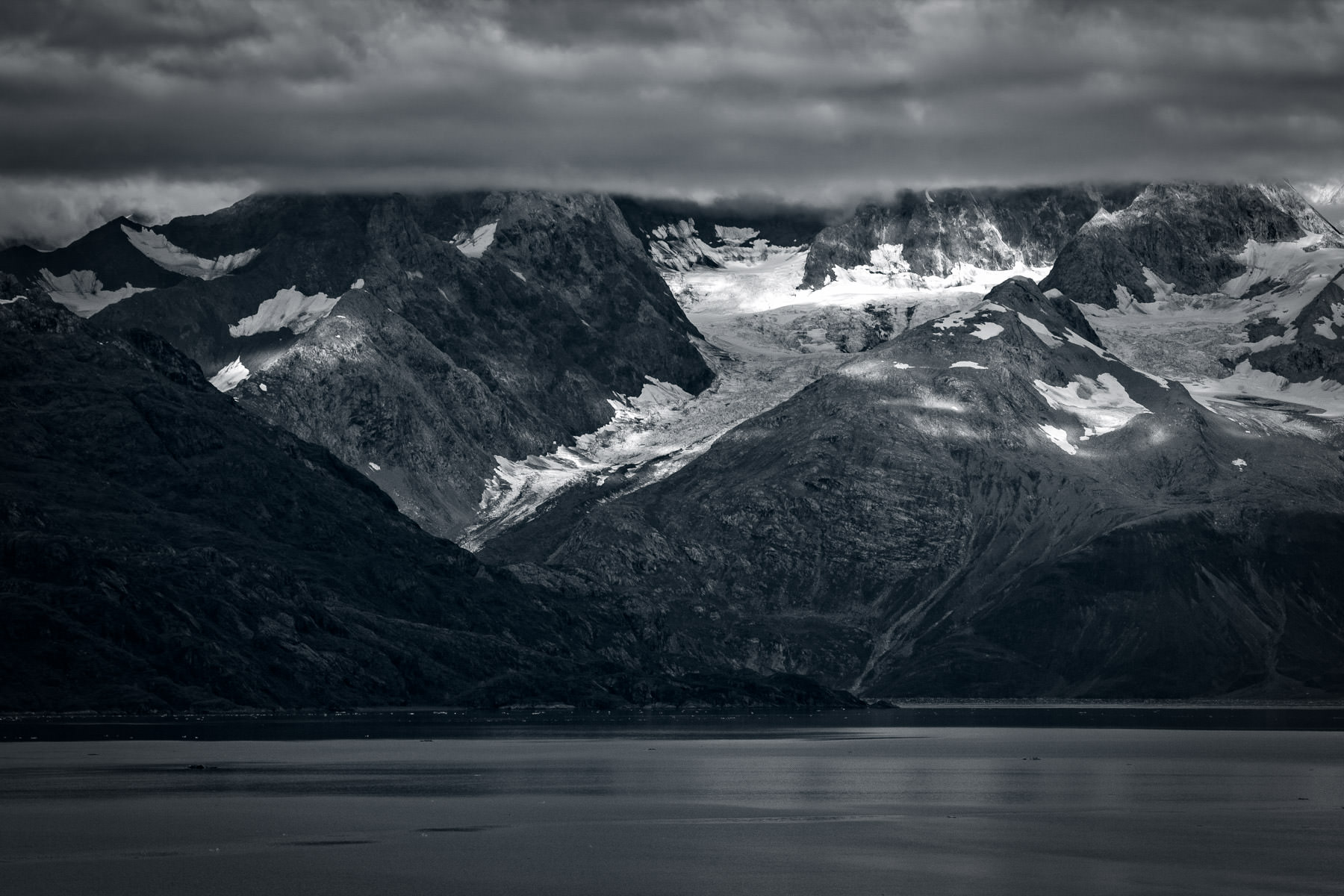 Mountains along the shoreline of Glacier Bay rise into the early morning clouds at Glacier Bay National Park, Alaska.