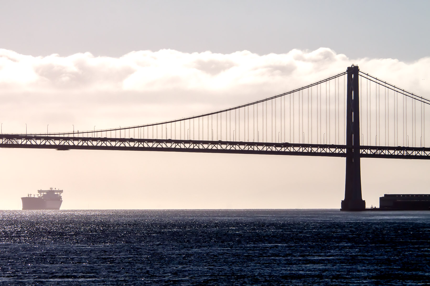 A cargo ship passes under the Golden Gate Bridge on its way to San Francisco Bay in the early morning sunlight.