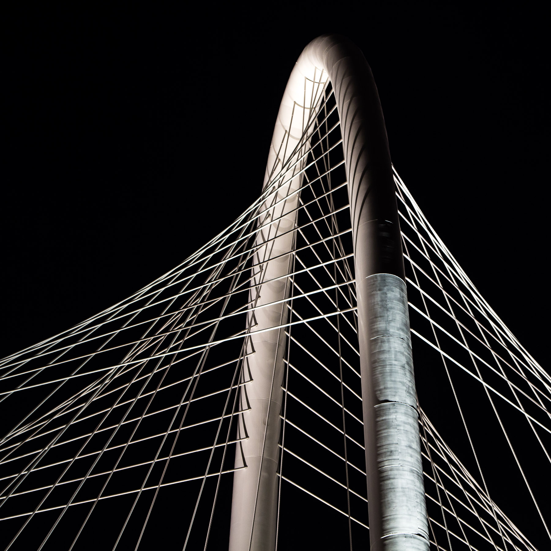 Nighttime detail of the arch and cables of the Santiago Calatrava-designed Margaret Hunt Hill Bridge, Dallas.