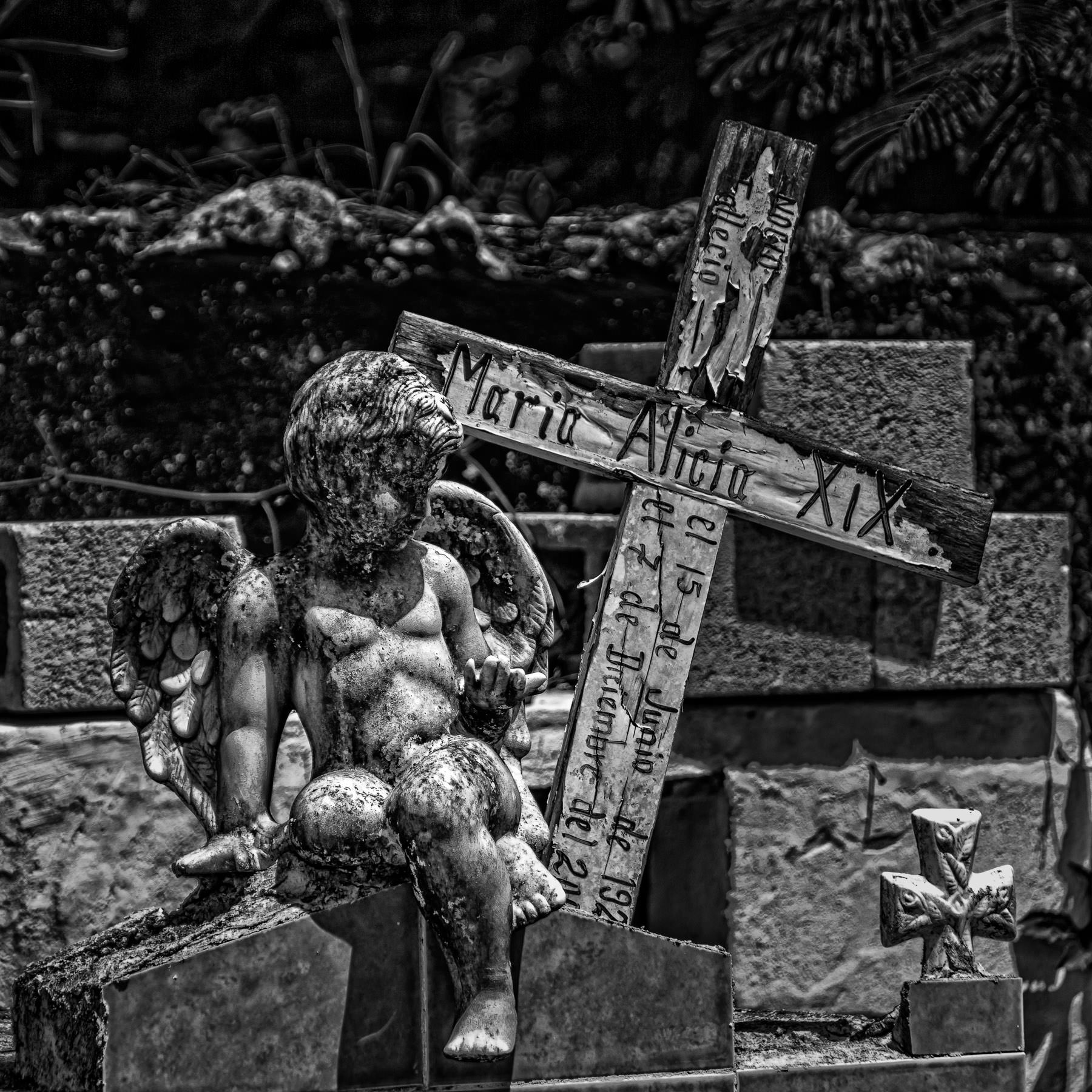 A simple hand-carved wooden cross marks a grave in a cemetery in the small village of Dzemul, Yucatan, Mexico.