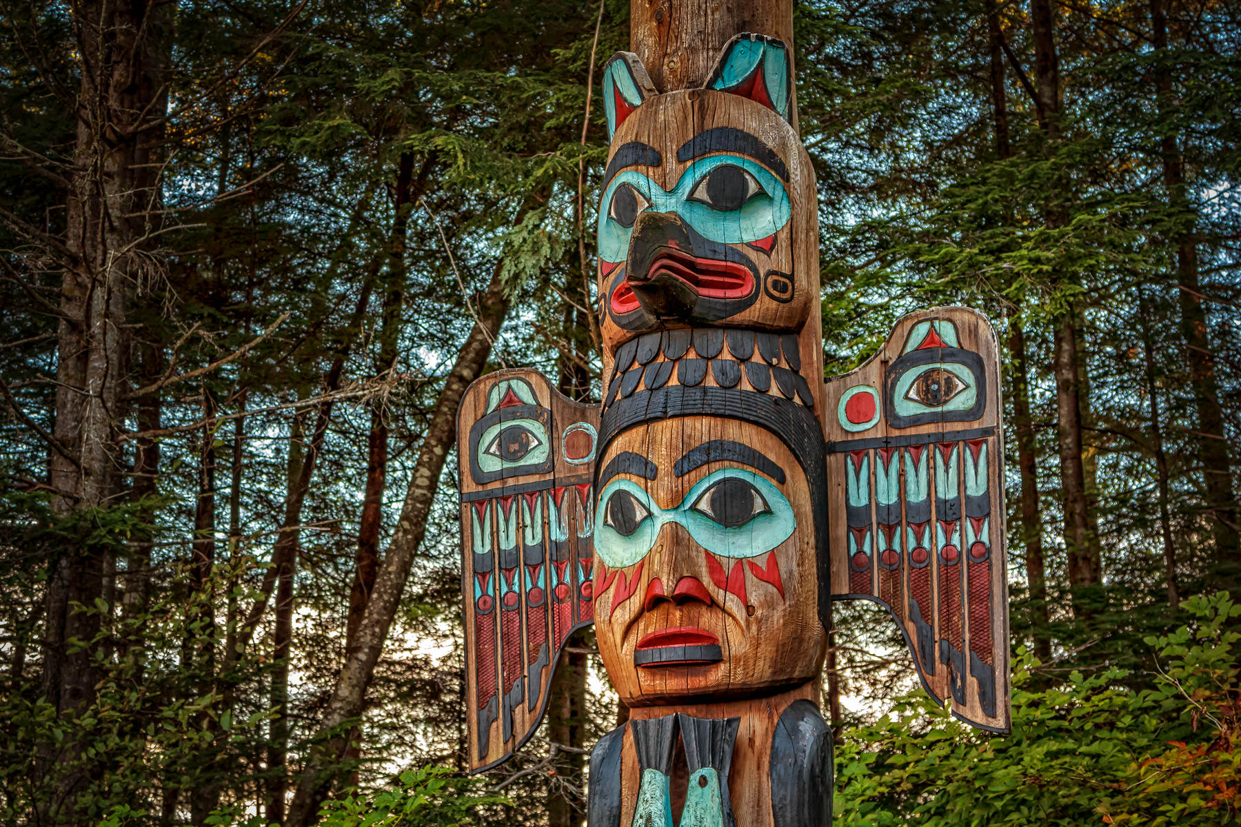 The Kadjuk Bird Pole at Ketchikan, Alaska's Totem Bight State Park depicts Raven forming the headdress of his wife, the Fog Woman, as she holds two salmon.