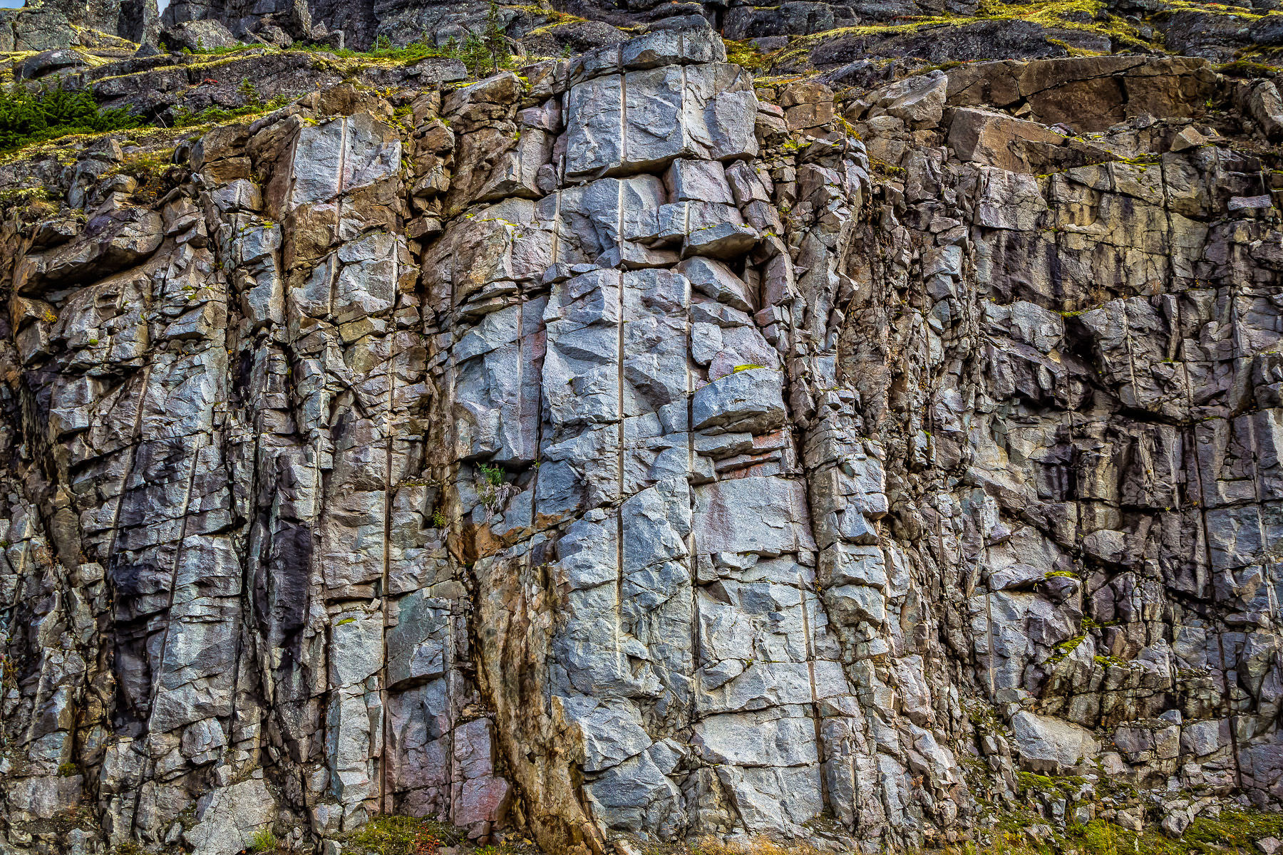 Cracked rocks showing vertical boreholes where explosives were placed to carve the Klondike Highway out of the rugged landscape of Alaska near the border with British Columbia, Canada.