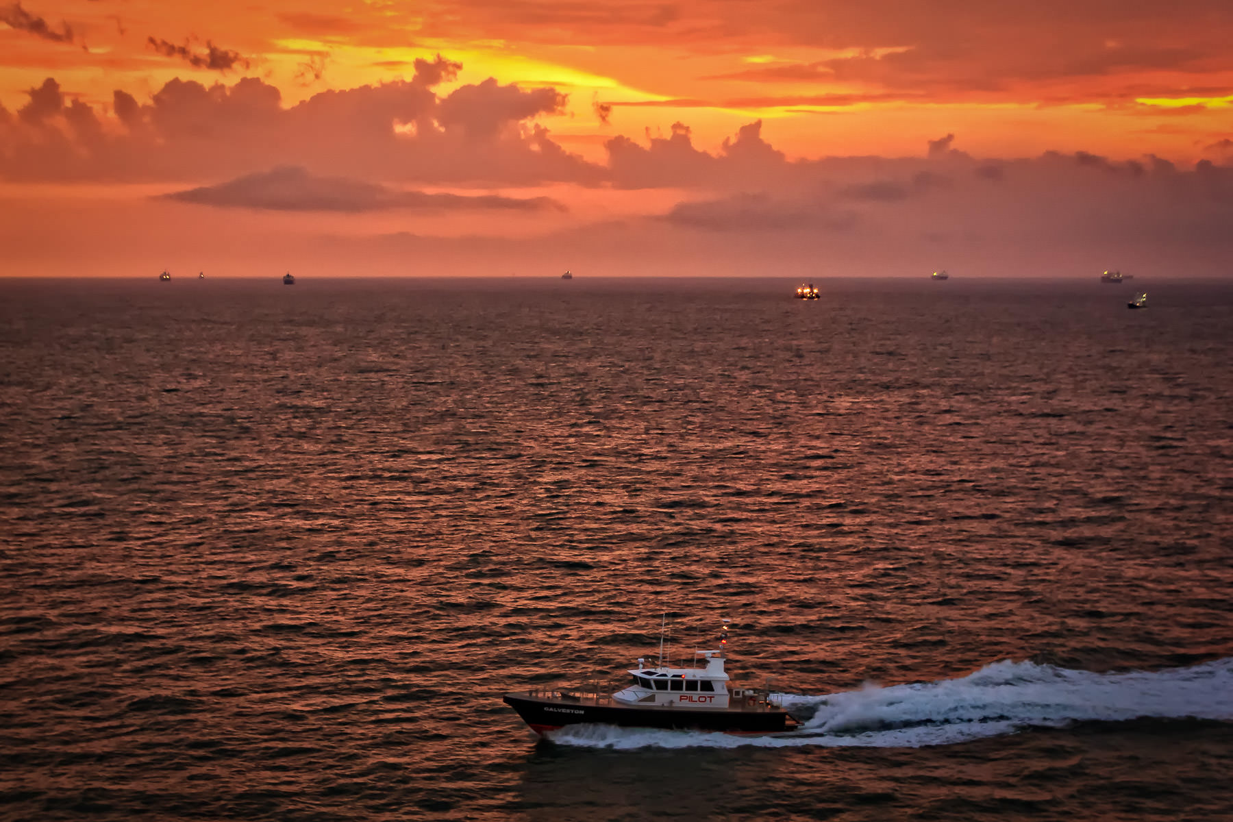 A Port of Galveston, Texas pilot boat carries a port pilot to a ship as dawn breaks over the Gulf of Mexico.