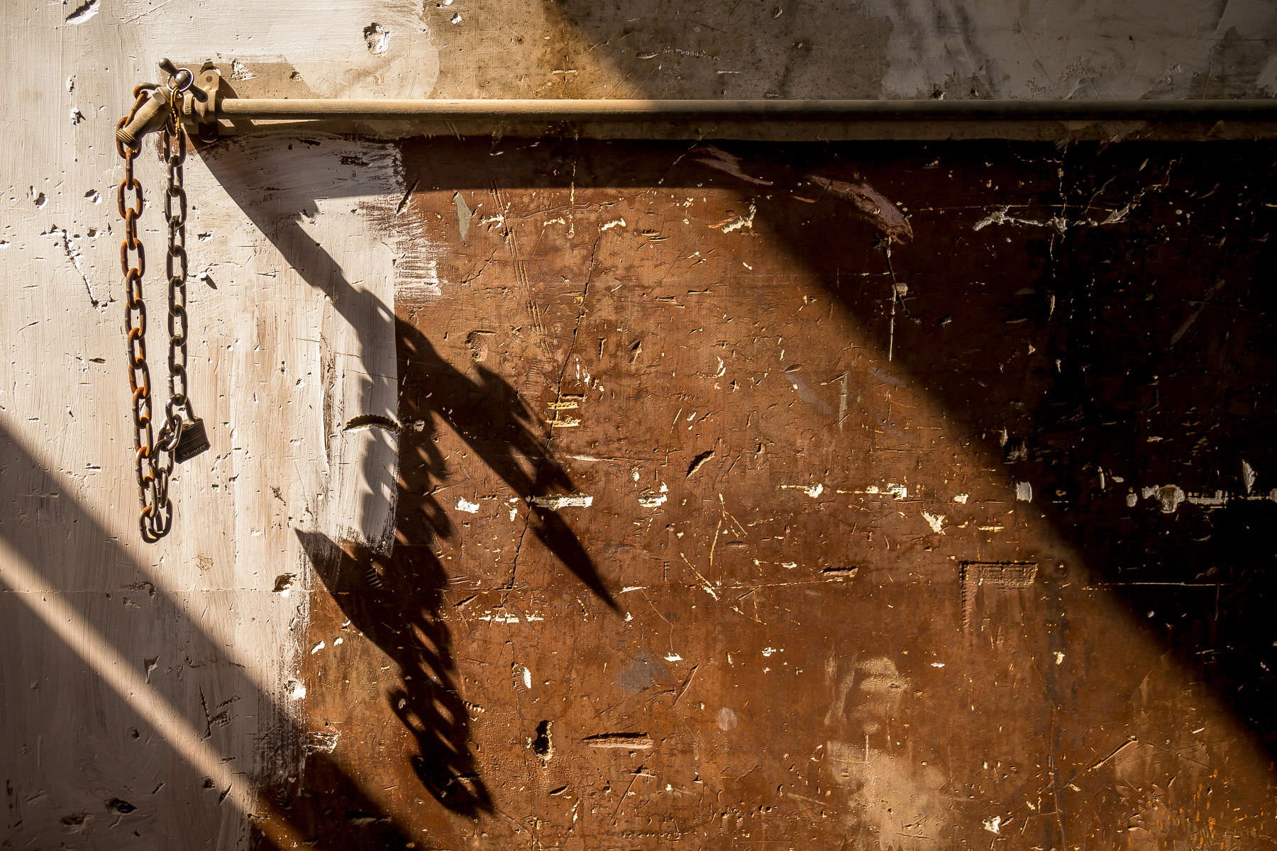 A rusting chain hanging from a pipe casts a shadow inside the abandoned Long Machine Tool Company building in Deep Ellum, Dallas, Texas.
