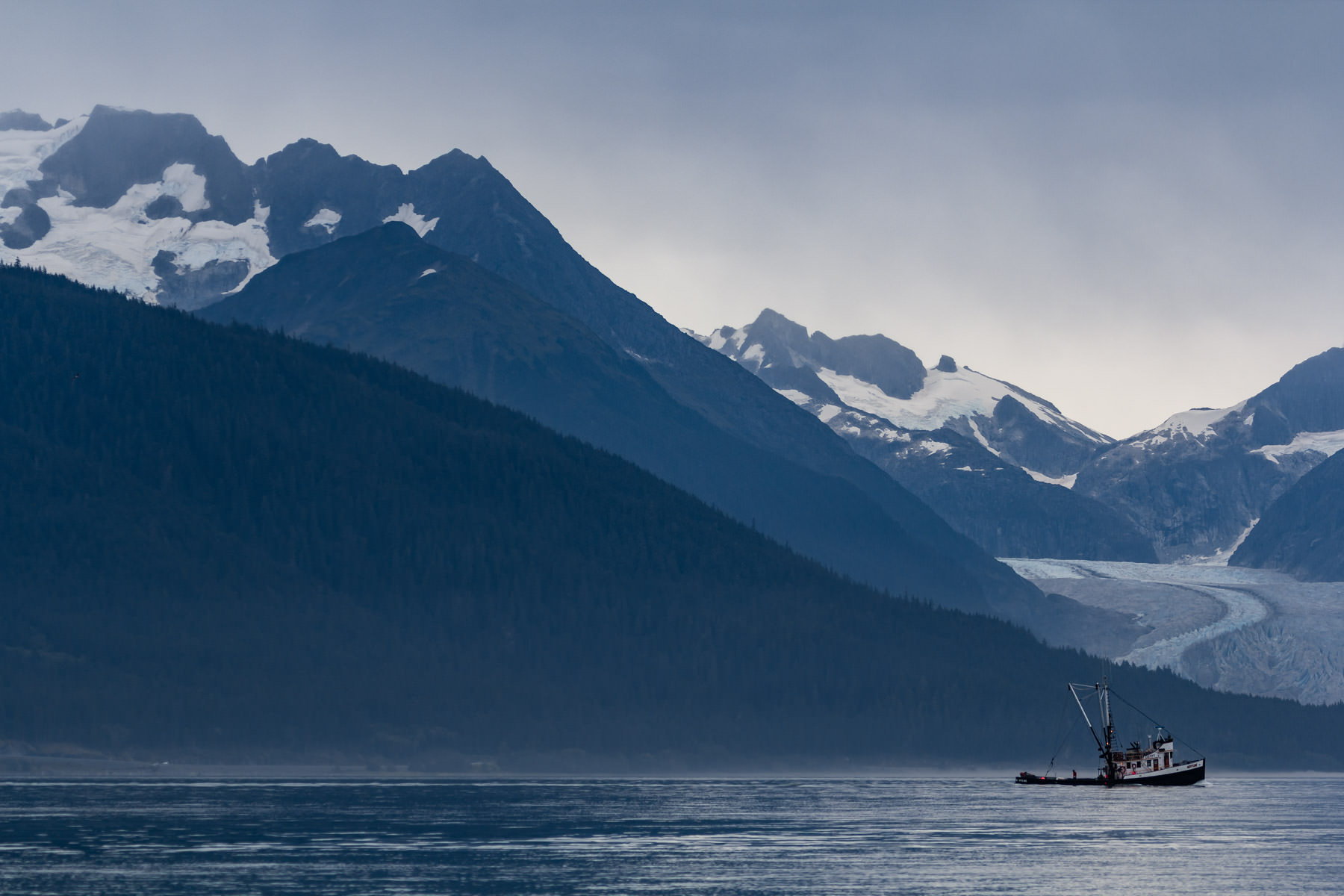 A fishing boat motors through a channel near Juneau, Alaska on a cold, overcast day.