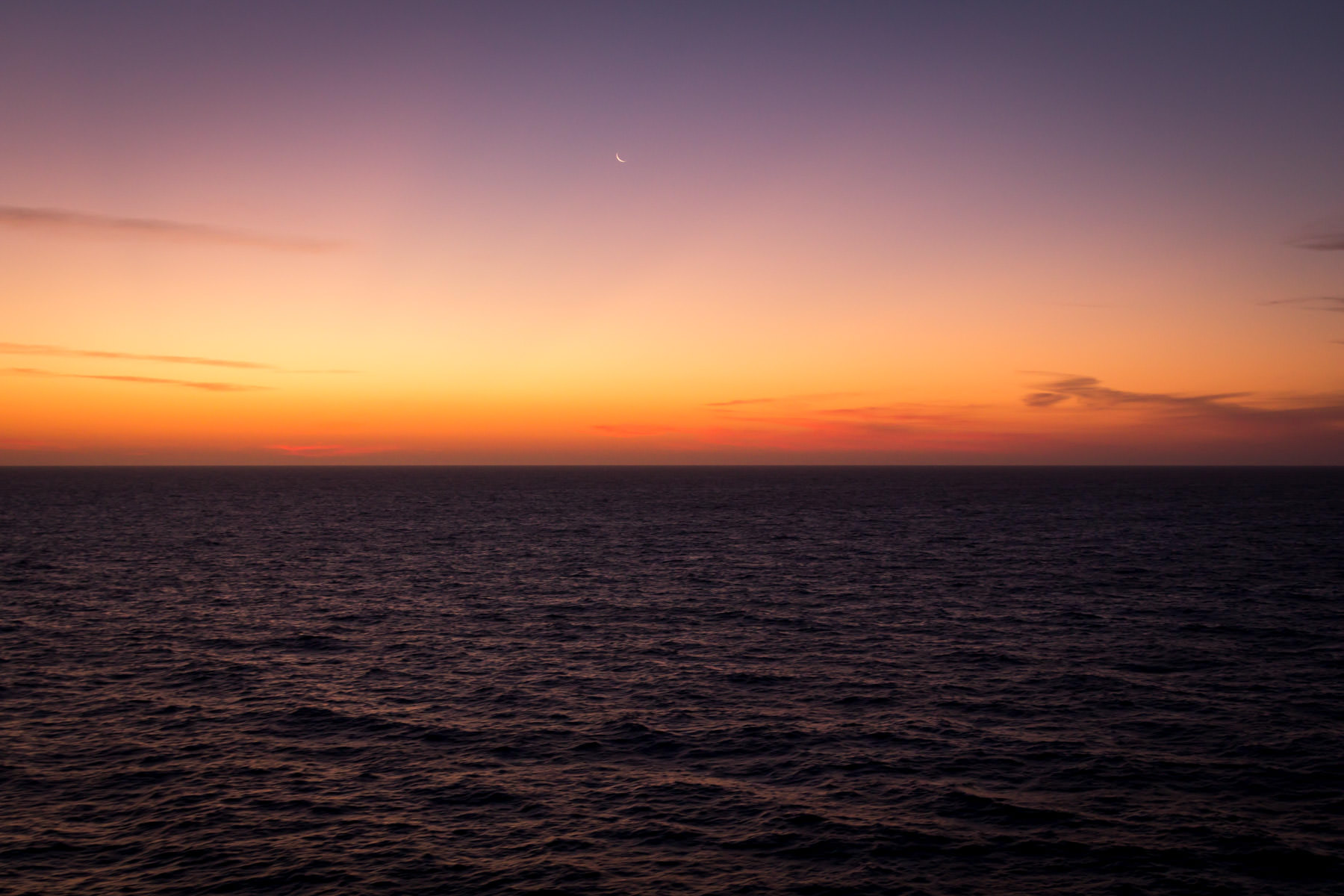 The first light of the sun begins to creep over the horizon somewhere in the Gulf of Mexico.