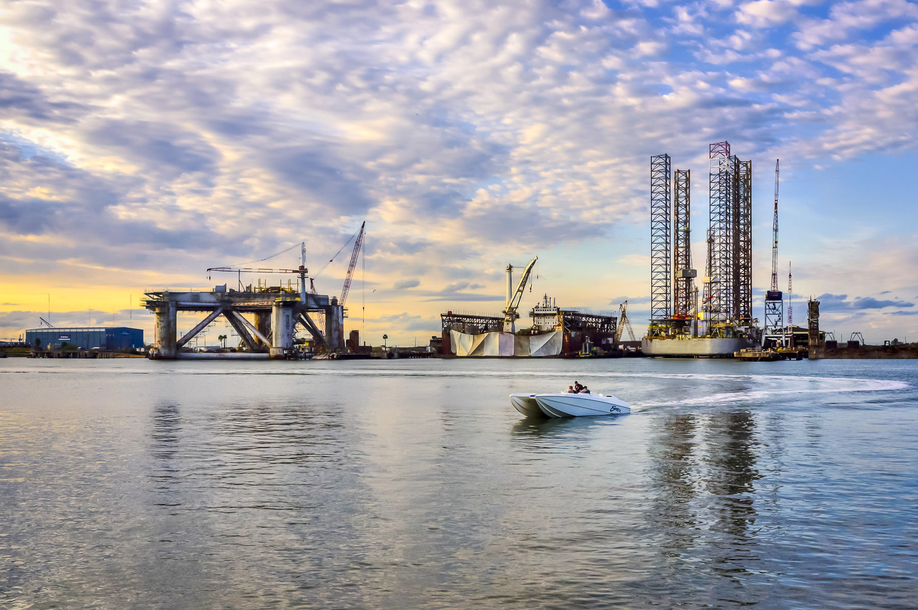 Oil platforms in drydocks at Pelican Island, Texas, as the sun sets on Galveston Harbor.