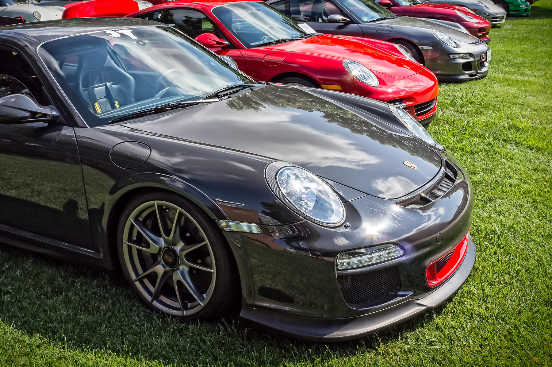 Several Porsche 911s (and related variants) at Dallas' Autos in the Park at Cooper Aerobics Center.
