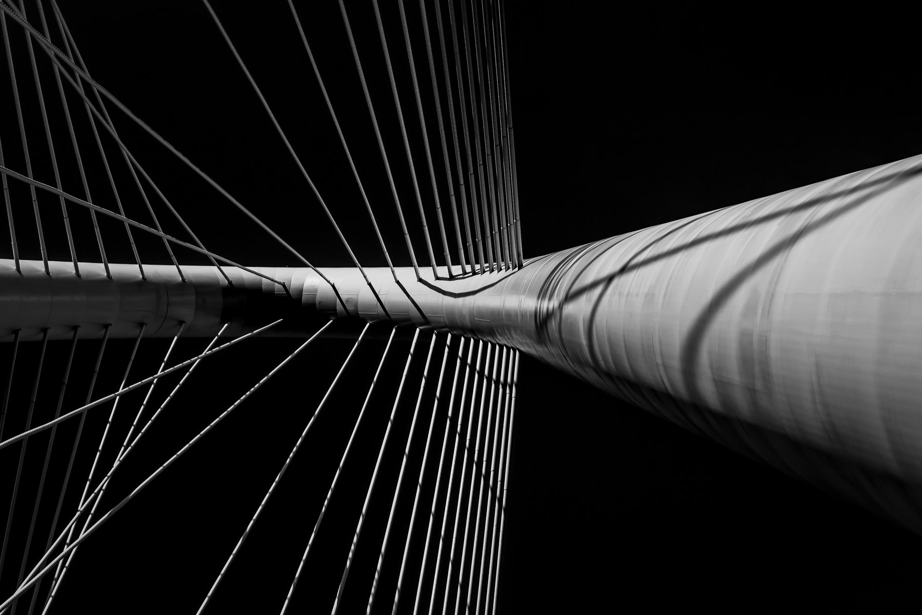 Abstract detail of the Santiago Calatrava-designed Margaret Hunt Hill Bridge's arch and attached cables rising into the Dallas sky.
