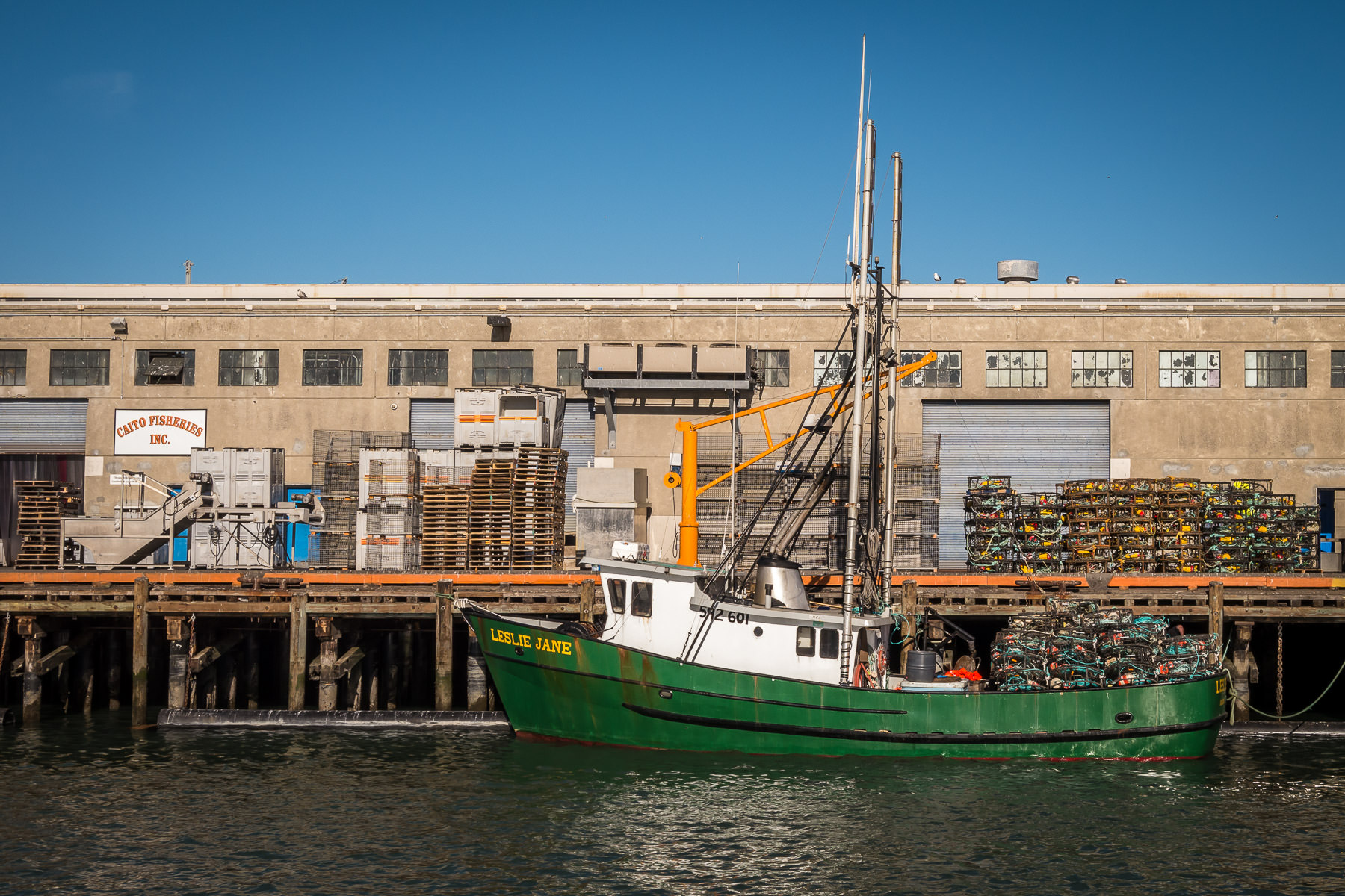 A dungeness crab fishing boat loaded with crab pots prepares to head out for the day at San Francisco's Fisherman's Wharf.