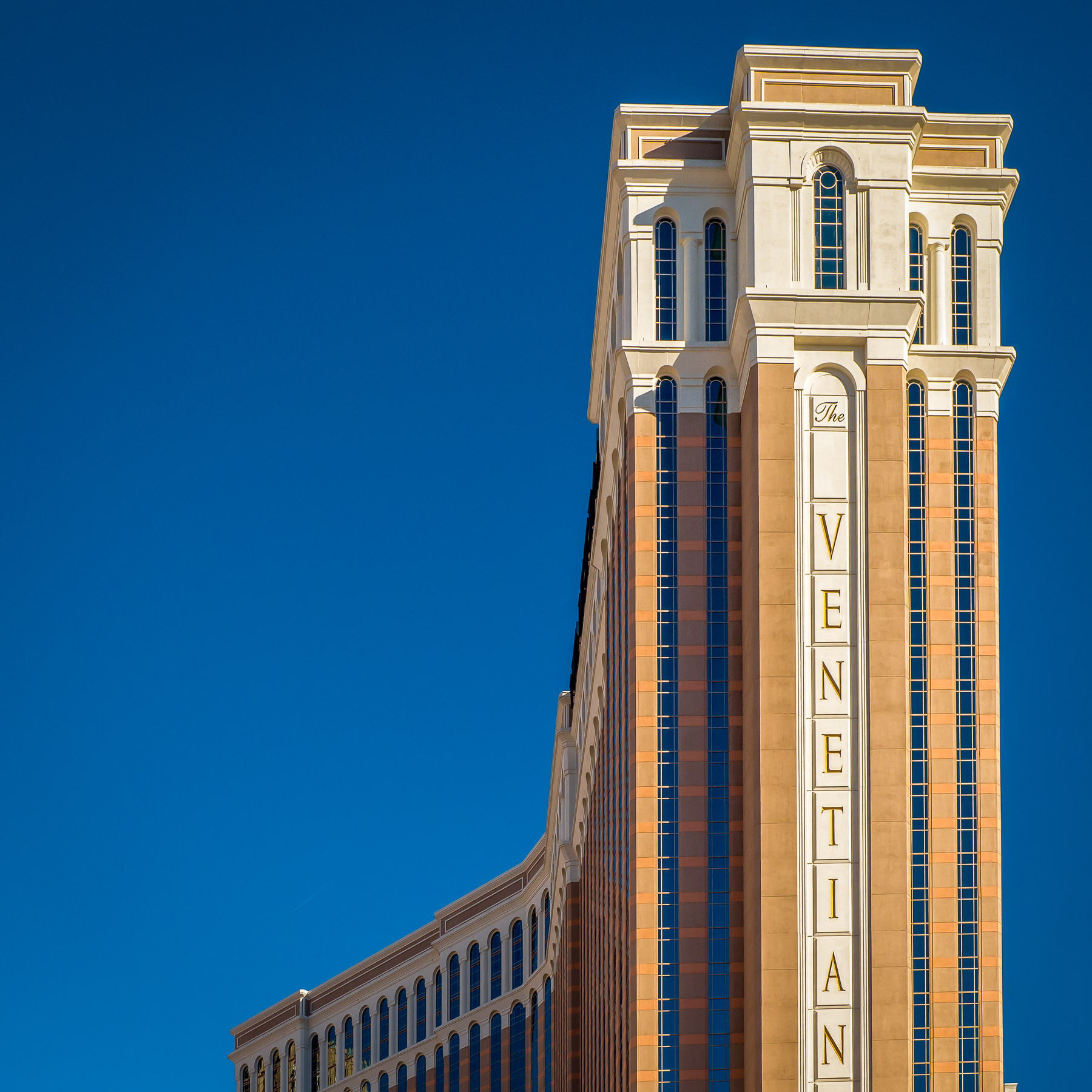 The main tower of The Venetian rises into the clear blue sky over Las Vegas.