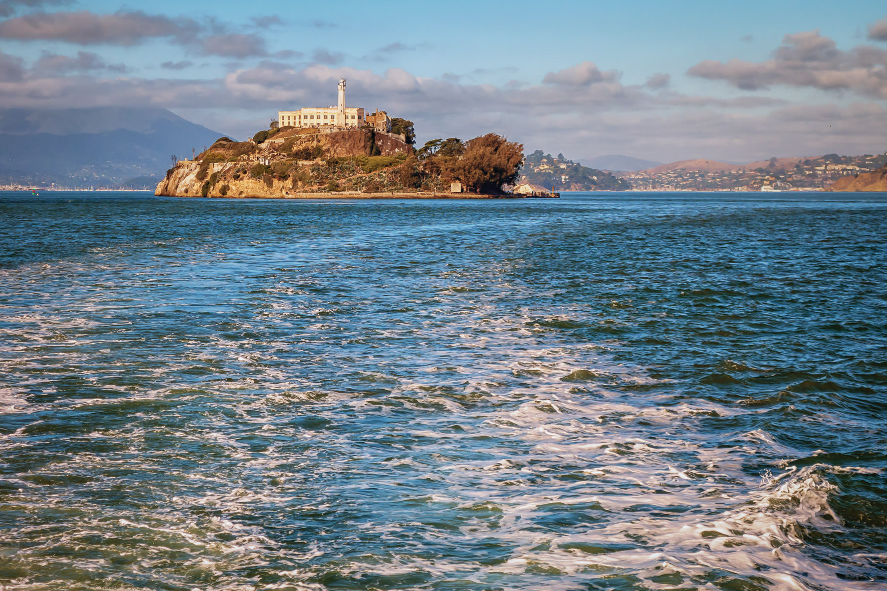 Alcatraz Island recedes in the distance of San Francisco Bay as seen from the deck of the excursion boat Alcatraz Flyer.