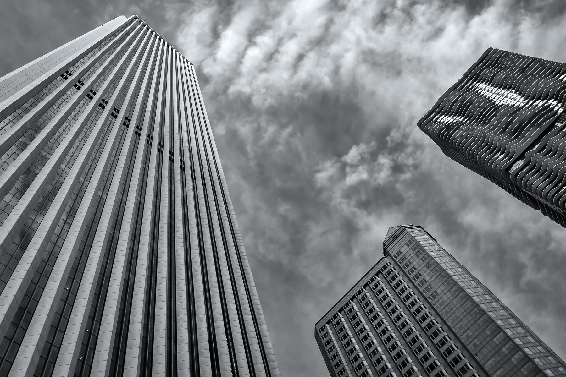 Chicago's Aon Center—the city's third-tallest skyscraper—dramatically rises into the sky, joined by the neighboring Fairmont Chicago hotel (center) and the Aqua tower (right).