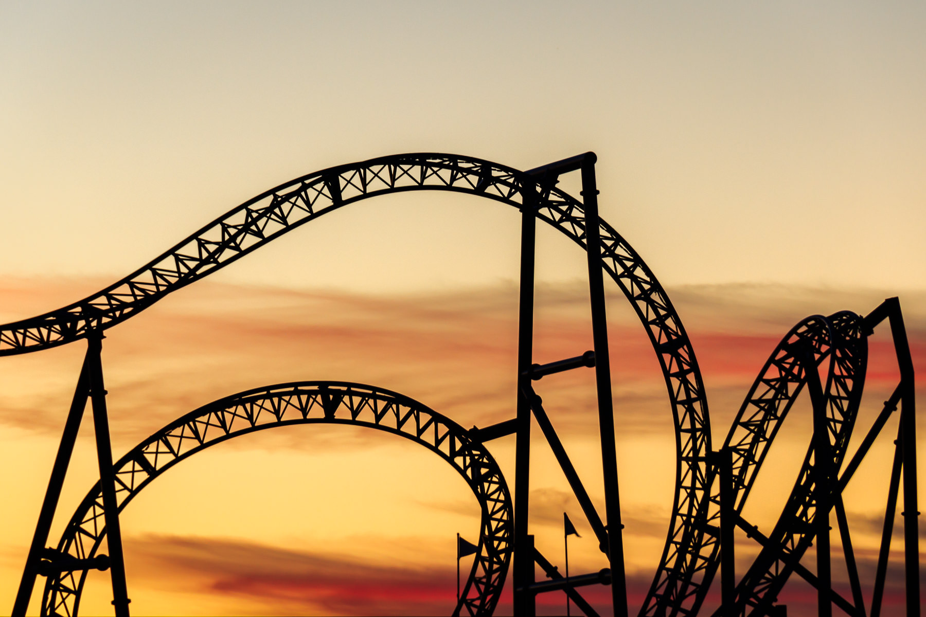 The curving, twisting track of the roller coaster at Galveston, Texas' Pleasure Pier, backlight by the rising sun.