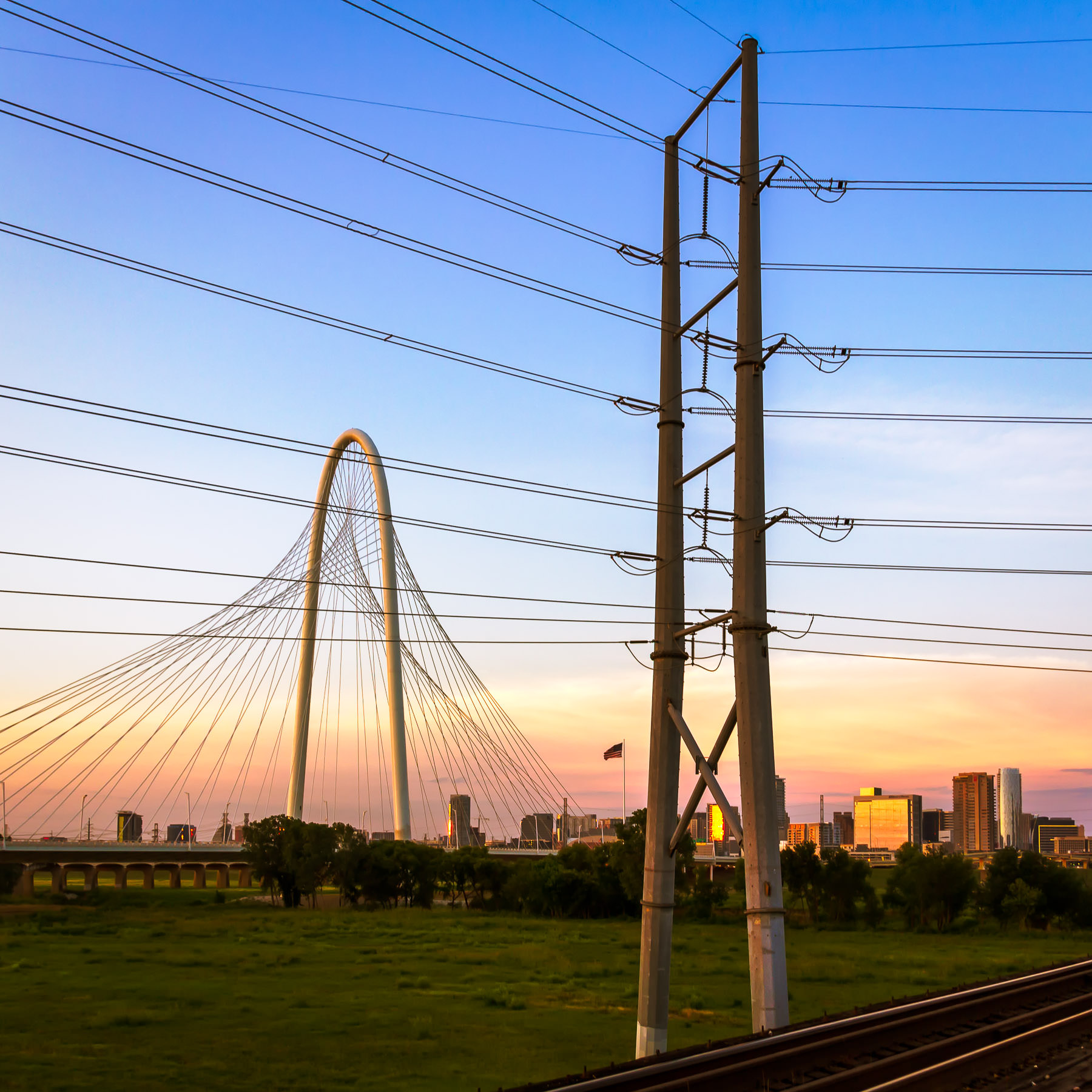 Dallas' Margaret Hunt Hill Bridge and a neighboring power pylon in the Trinity River floodplain as the sun sets on the city.