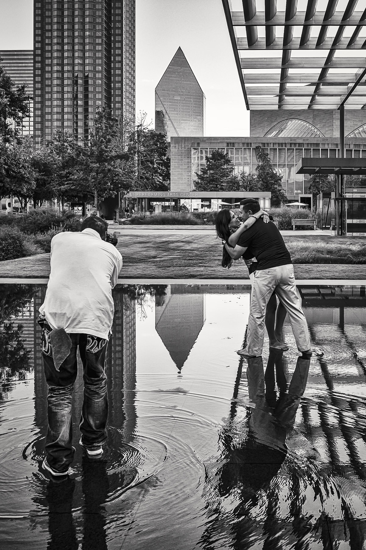 A photographer photographs a couple kissing in the reflecting pool at the Winspear Opera House in the Dallas Arts District.