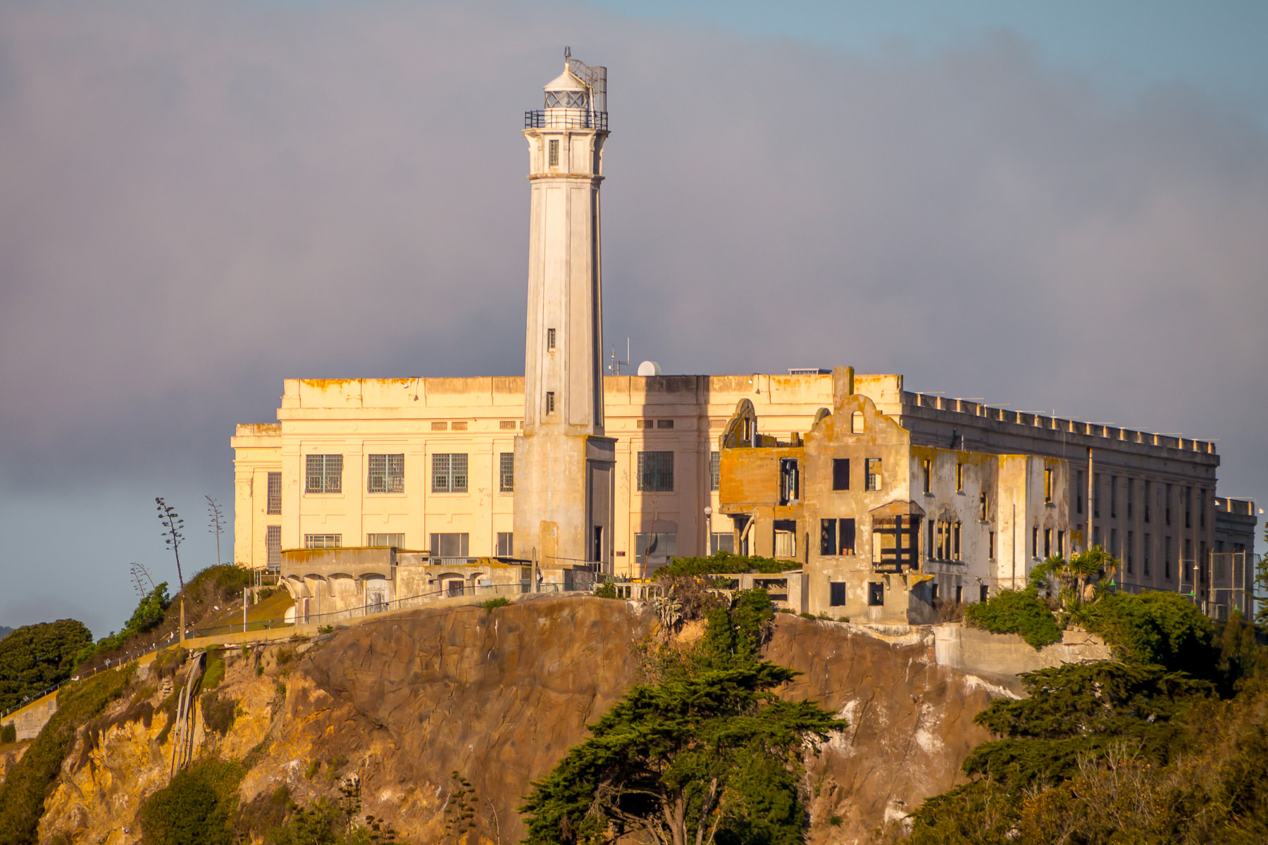 The Alcatraz Island Light catches the morning sun as it rises above the crumbling remains of the long-closed Alcatraz Federal Penitentiary, San Francisco.