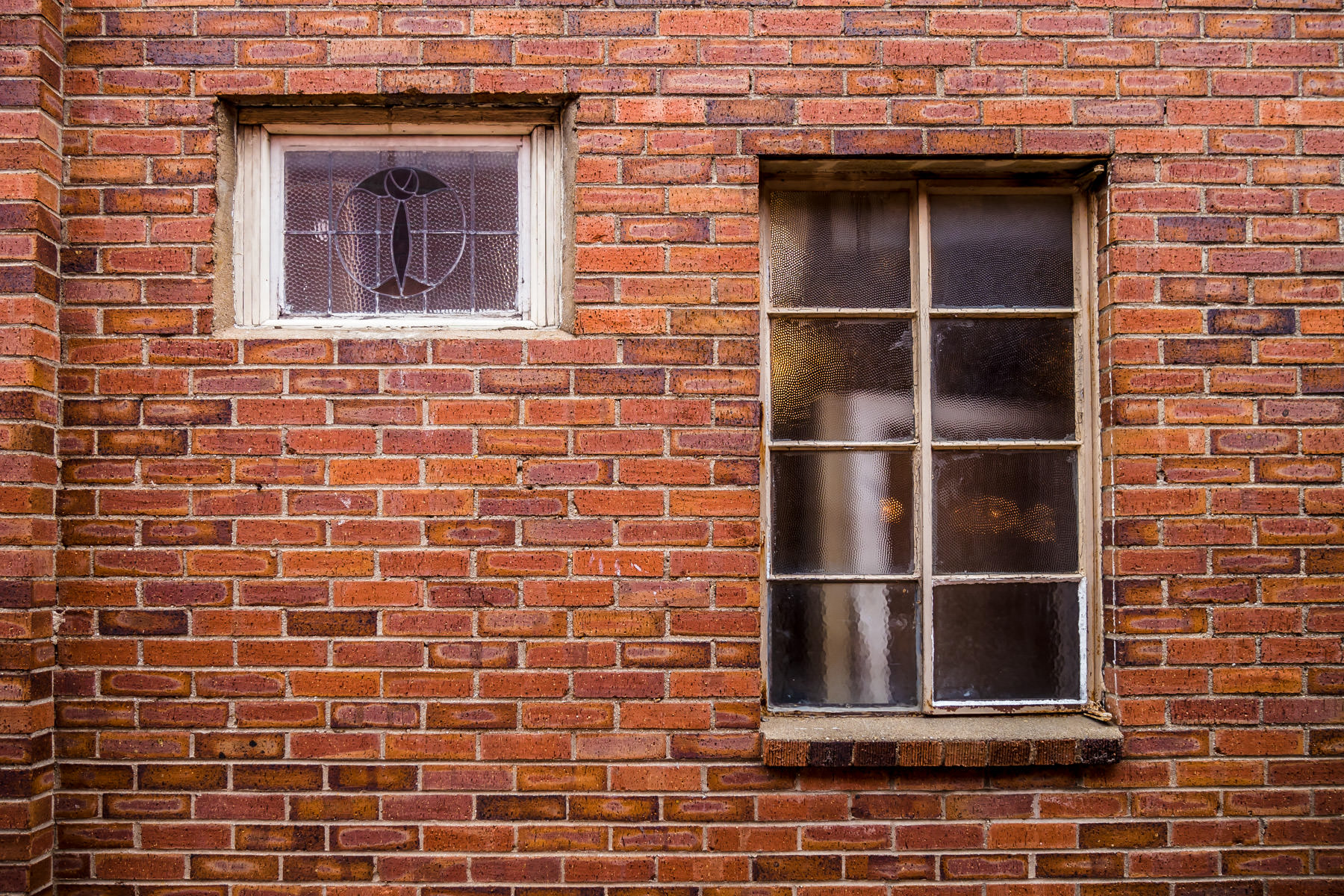 Two different sized windows on the exterior of an old building in Downtown Grapevine, Texas.