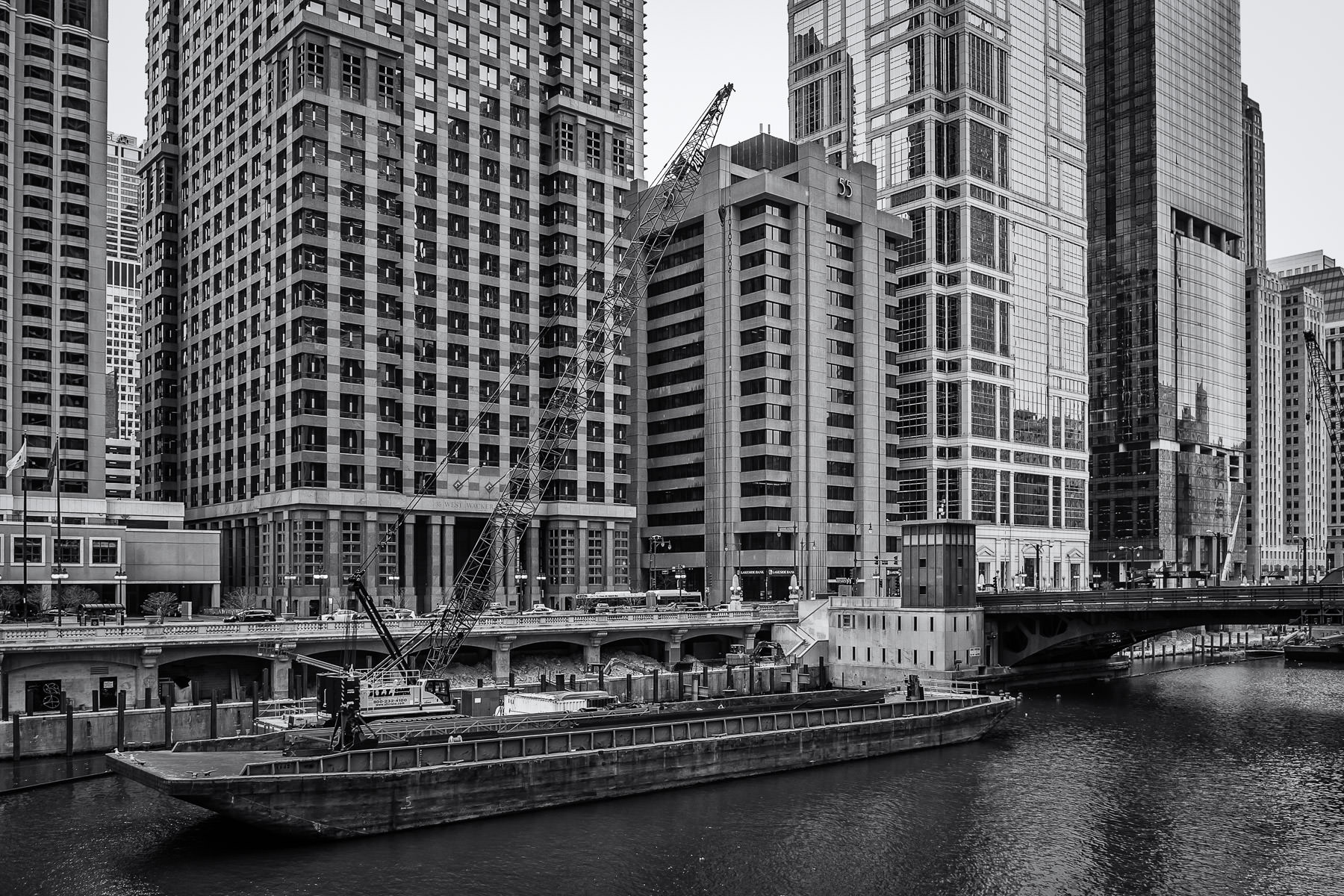 A barge with a crane atop it moored in the Chicago River adjacent to the Dearborn Street Bridge.