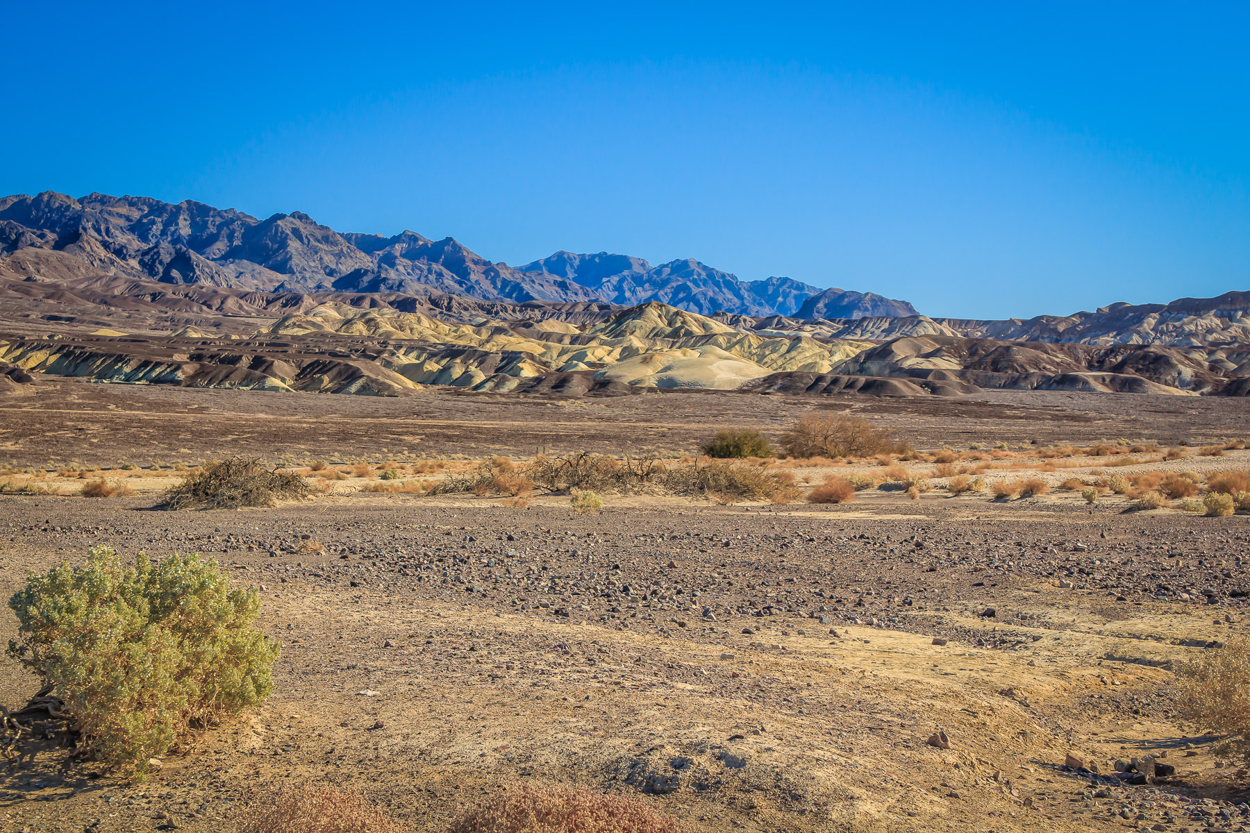 Mountains rise in the distance of Death Valley National Park's desert landscape.