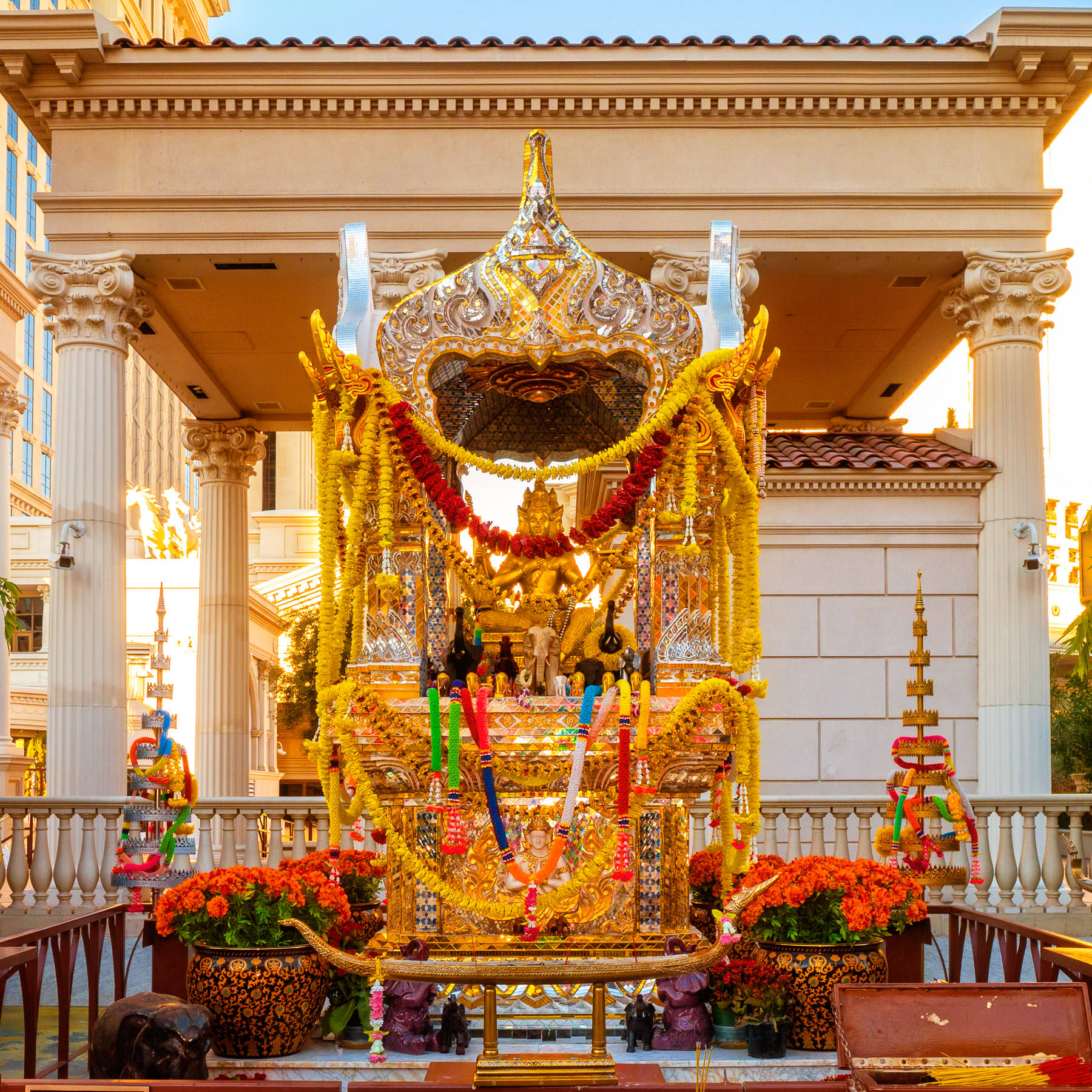 The Erawan Shrine (or Shrine of the Four-Faced Brahma) at Caesars Palace, Las Vegas, was built in 1984 and is a replica of the original in Bangkok, Thailand. It was donated by newspaper tycoons Mr. and Mrs. Kamphol Vacharaphol and Mr. Yip Hon, a prominent figure in Hong Kong and is considered a Hindu holy site. Visitors express gratitude for wishes granted by offering flowers, incense, money (which Caesars donates to charities in Thailand) or by placing small wooden elephants