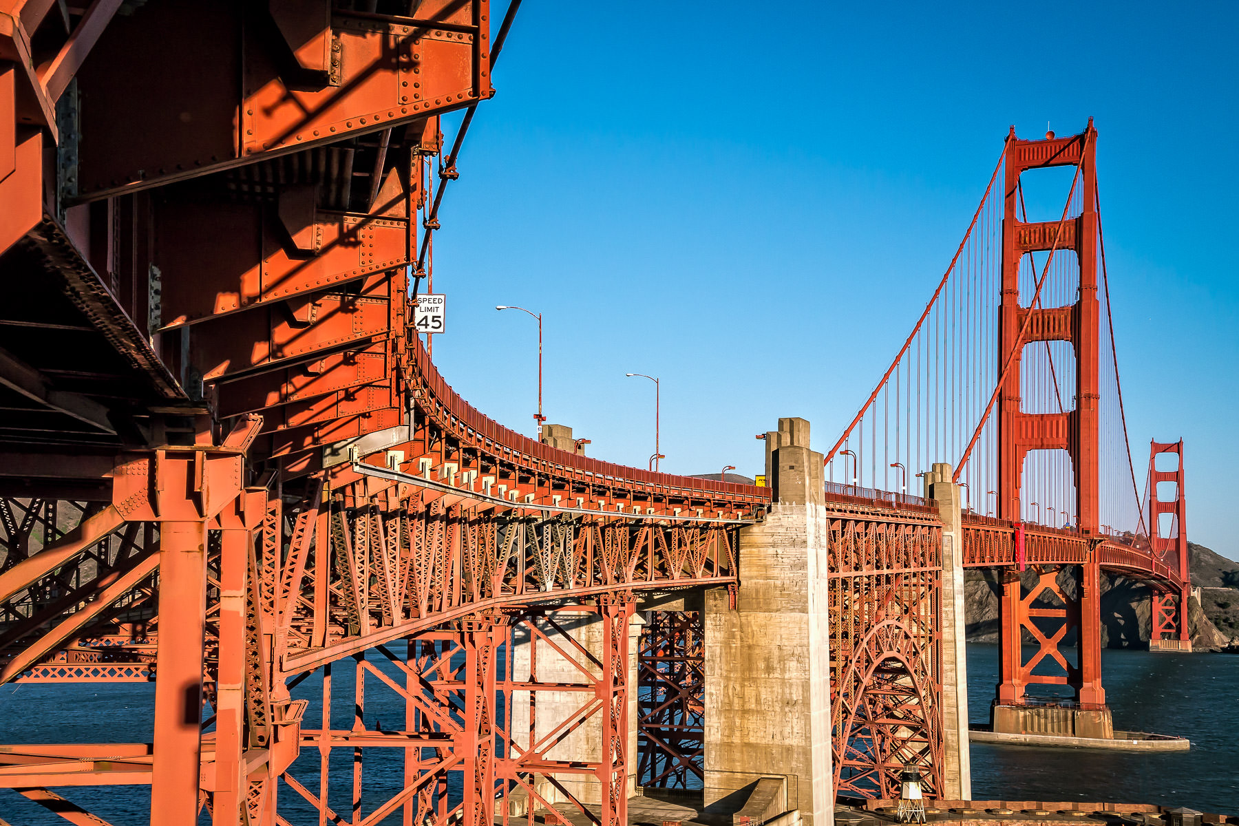 The iconic Golden Gate Bridge curves into the distance over the entrance to San Francisco Bay.
