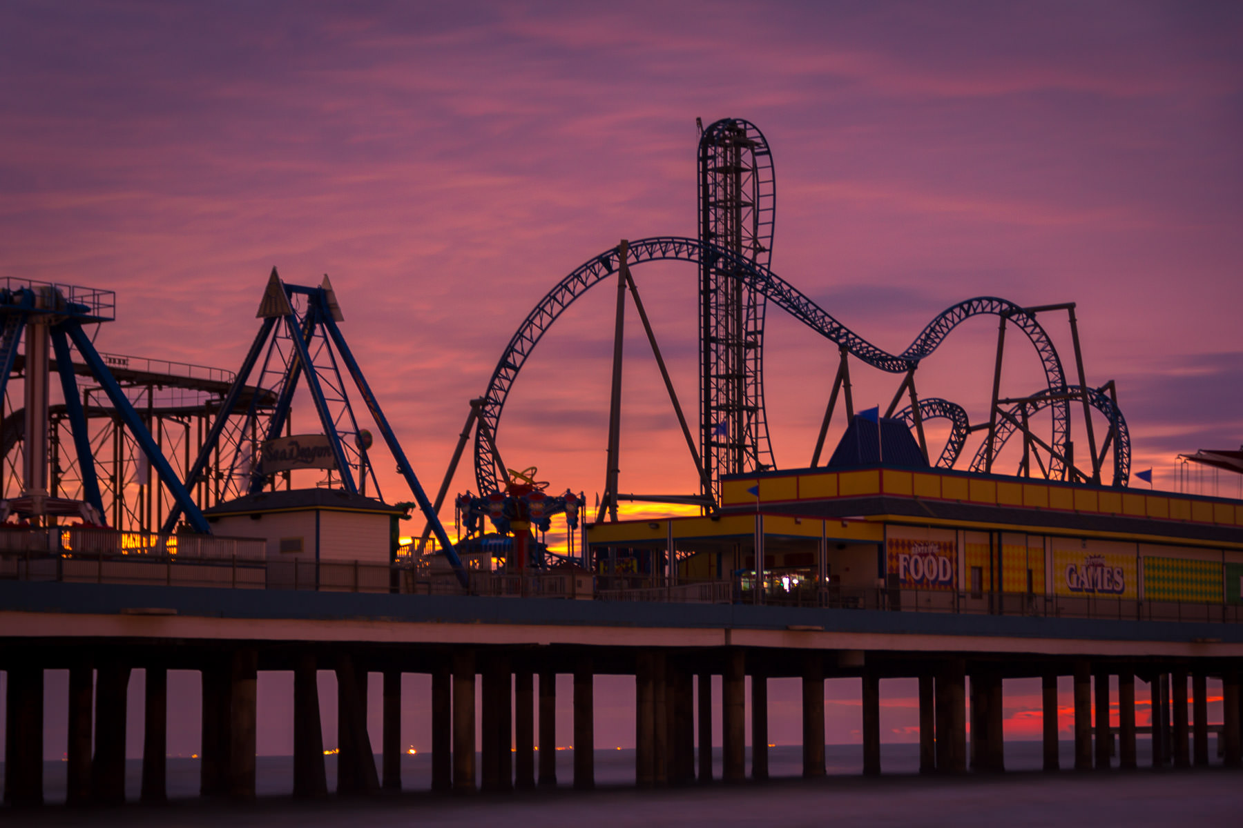 The sun rises over the Gulf of Mexico, behind Galveston, Texas' Historic Pleasure Pier.