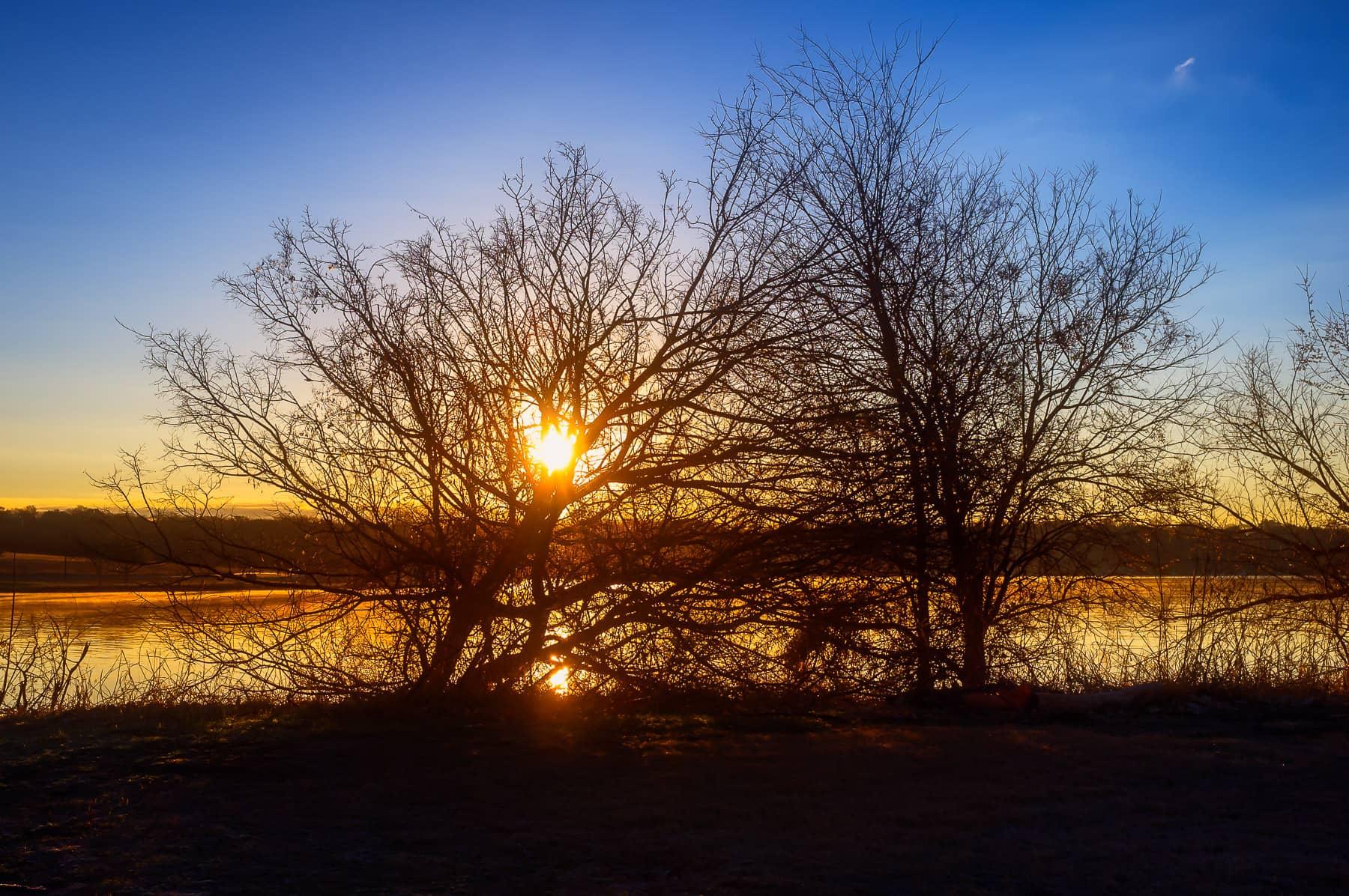 The sun rises over the east shore of Dallas' White Rock Lake.