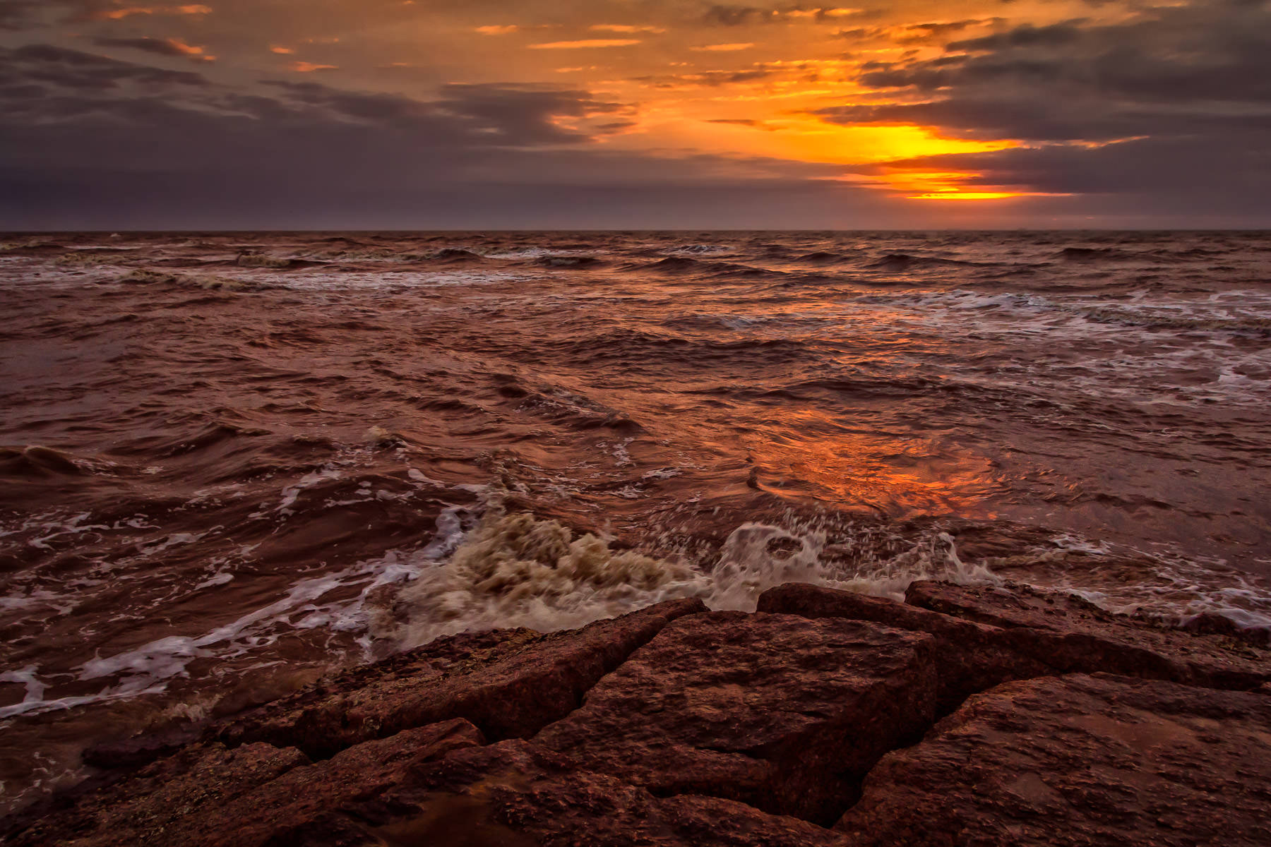 Waves crash into a granite jetty as the sun rises over the Gulf of Mexico just off the coast of Galveston, Texas.