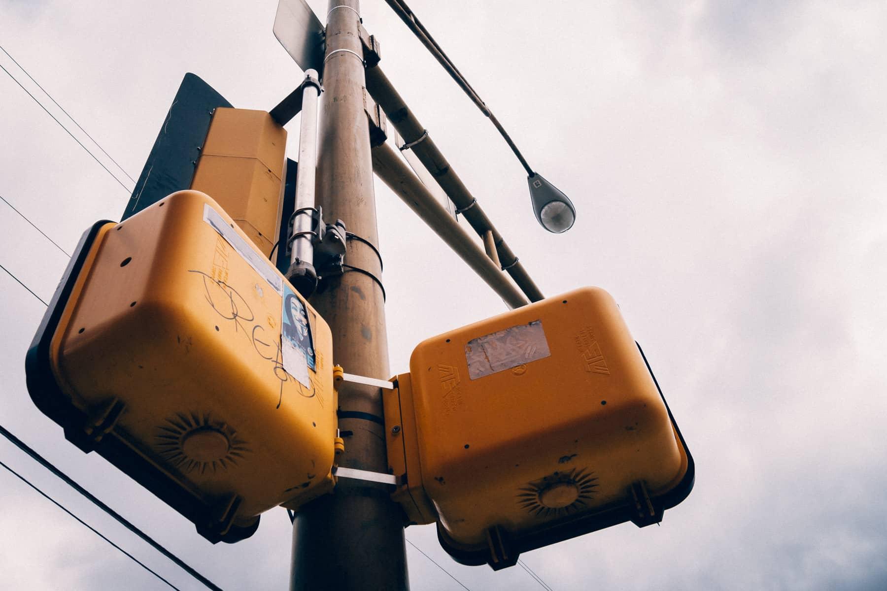 Pedestrian walk/don't walk signal boxes on a light pole in Dallas' Deep Ellum neighborhood.