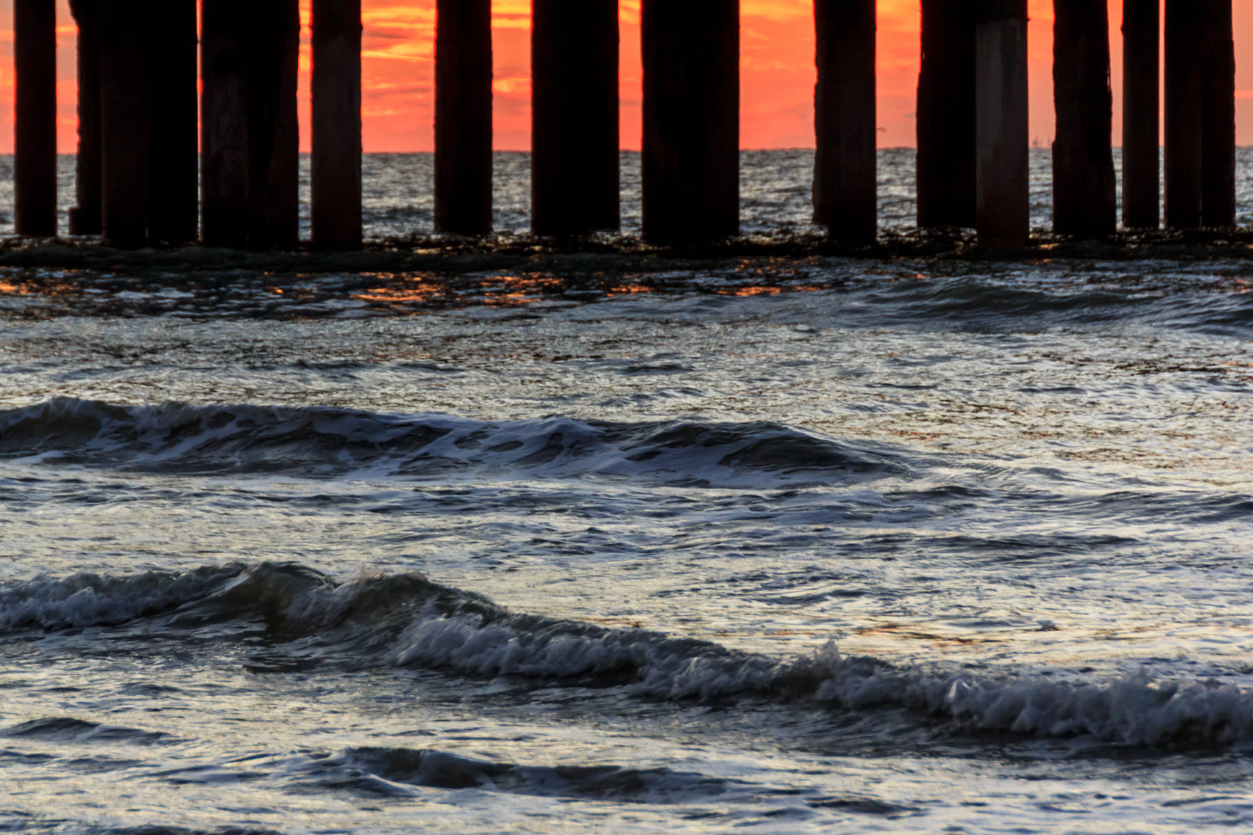 The sun rises over the Gulf of Mexico, silhouetting the supports of Galveston, Texas' Pleasure Pier.
