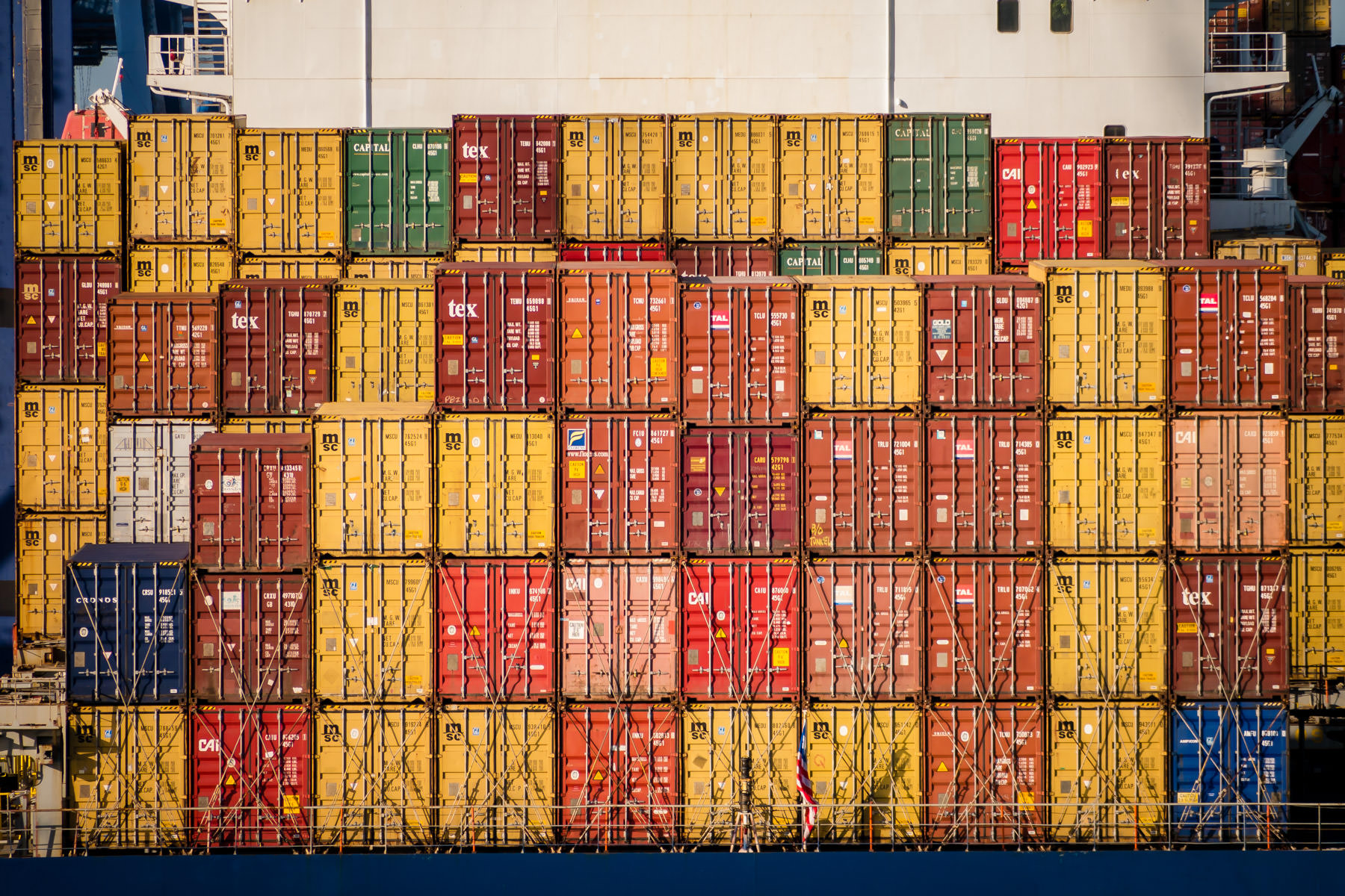 Multi-colored cargo containers wait to be unloaded from the ship HS Bach at the Port of Freeport, Bahamas.