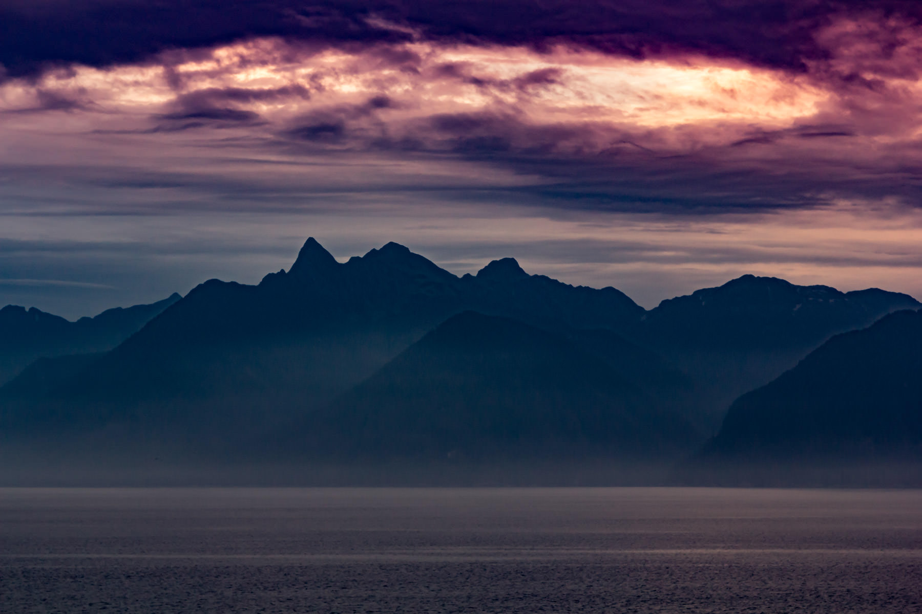 The morning sun lights up the sky beyond the mountain peaks of Alaska's Kuiu Island as seen from Chatham Strait.
