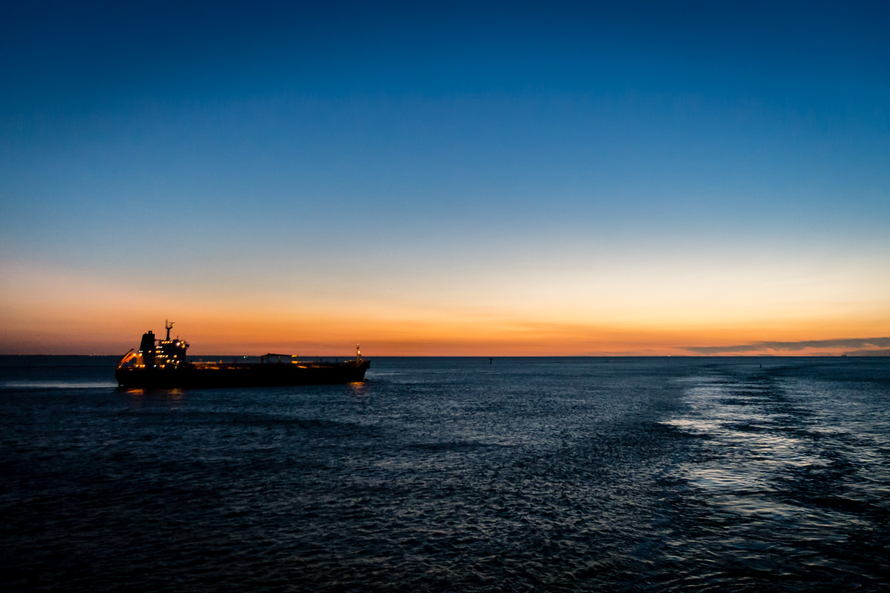 The chemical tanker Okhta Bridge transits Bolivar Roads just off the coast of Galveston, Texas, as the sun rises over the Gulf of Mexico.