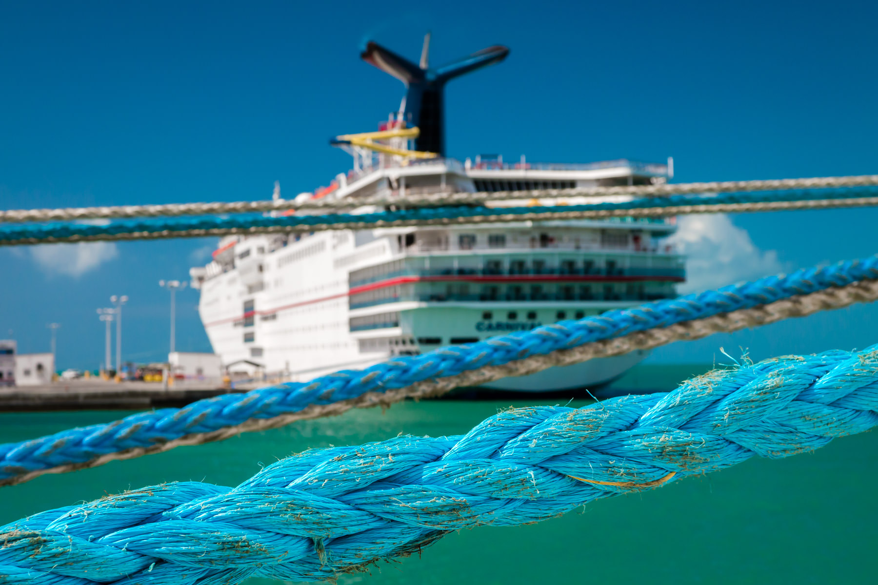 Hawsers tying up an adjacent cruise ship partially obscure the Carnival Ecstasy, dockside in Key West, Florida.