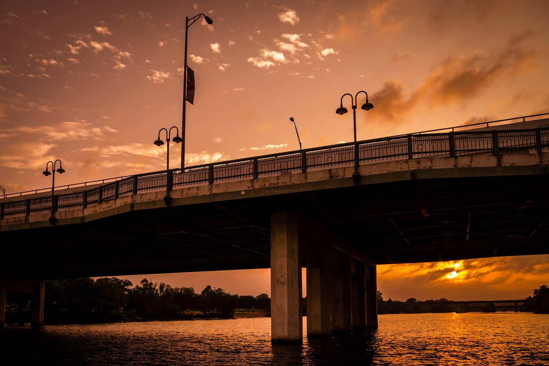 The sun sets on Austin's South First Street Bridge as it spans Lady Bird Lake.