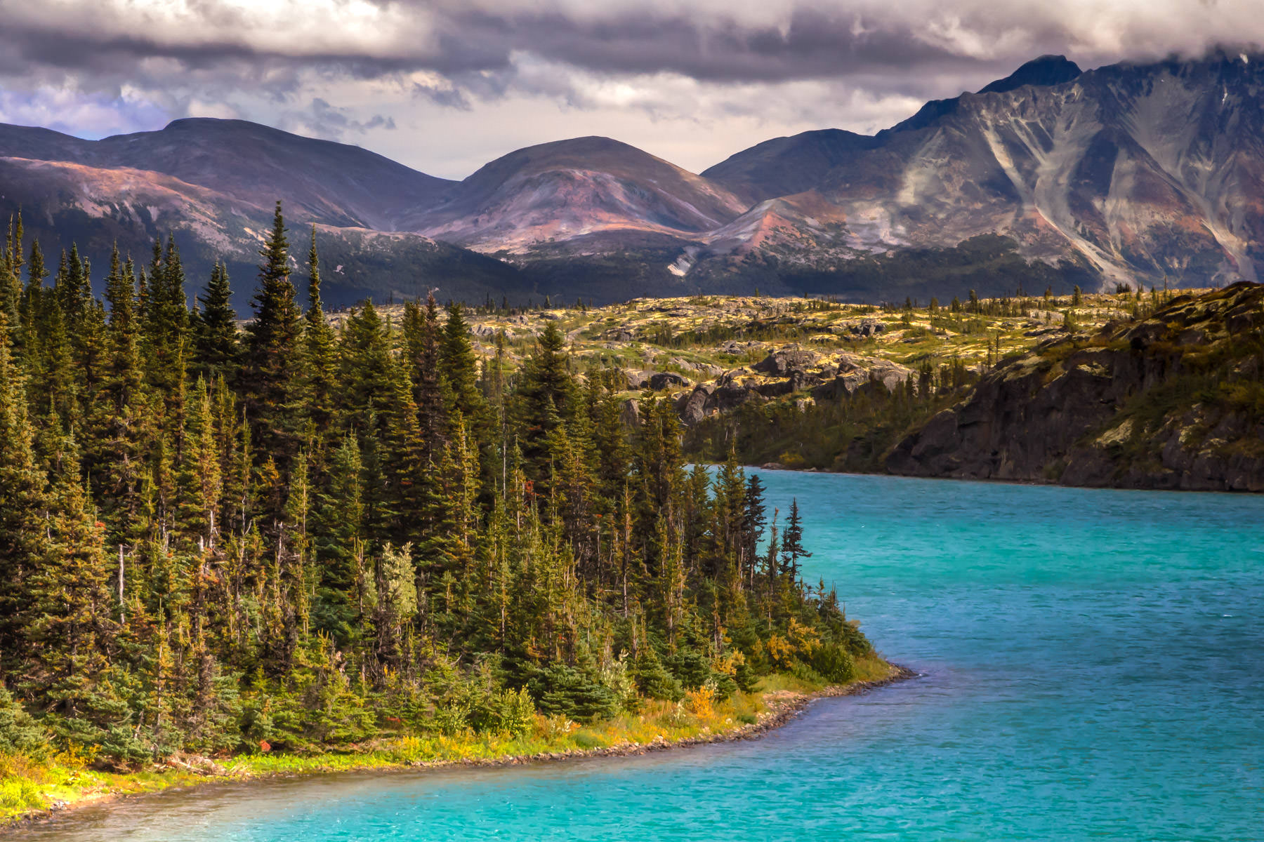 British Columbia's Bernard Lake, surrounded by towering pine trees and mountains along the Klondike Highway.