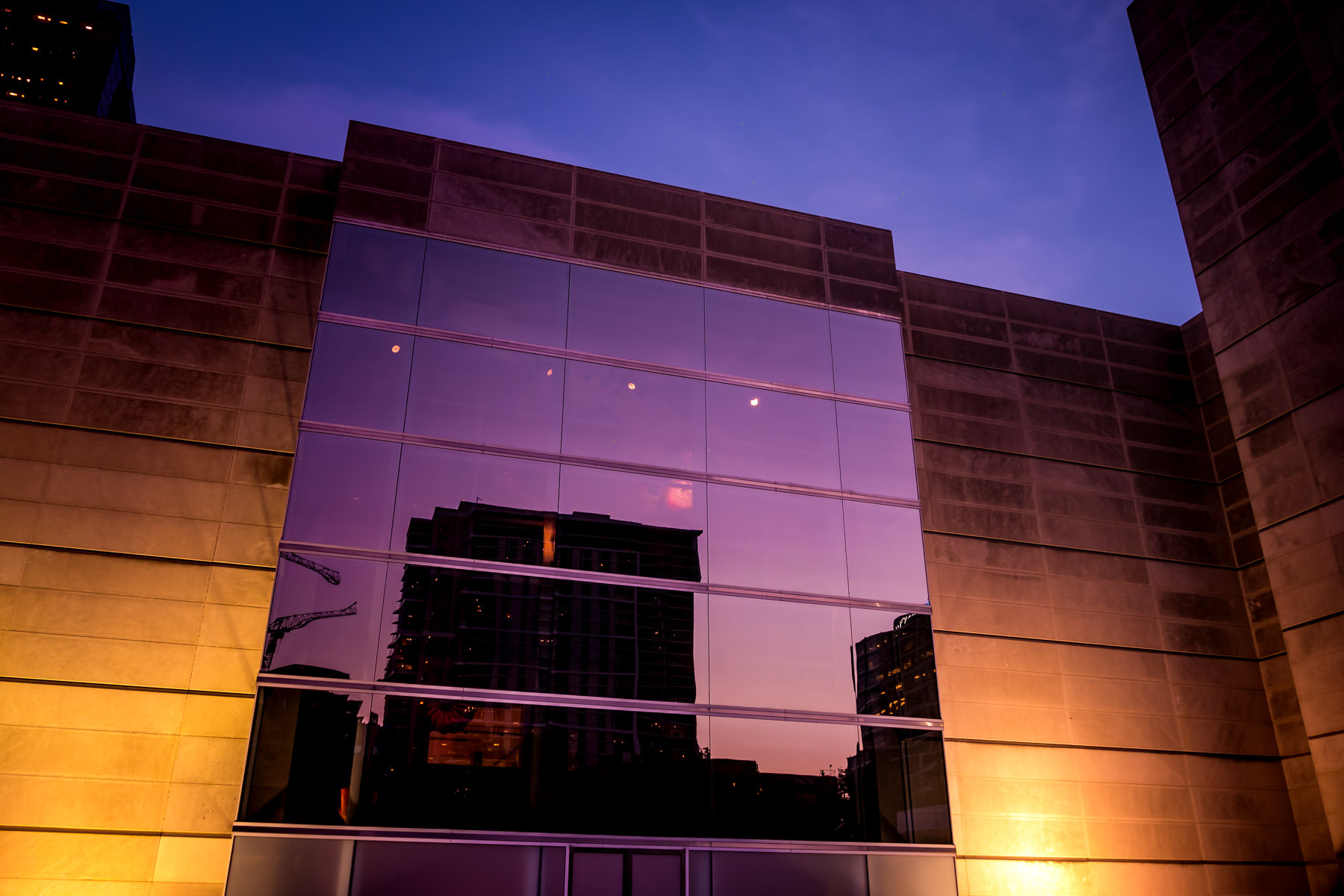 1900 McKinney is reflected in a huge multi-story window at the Dallas Museum of Art as the sun sets on North Texas.