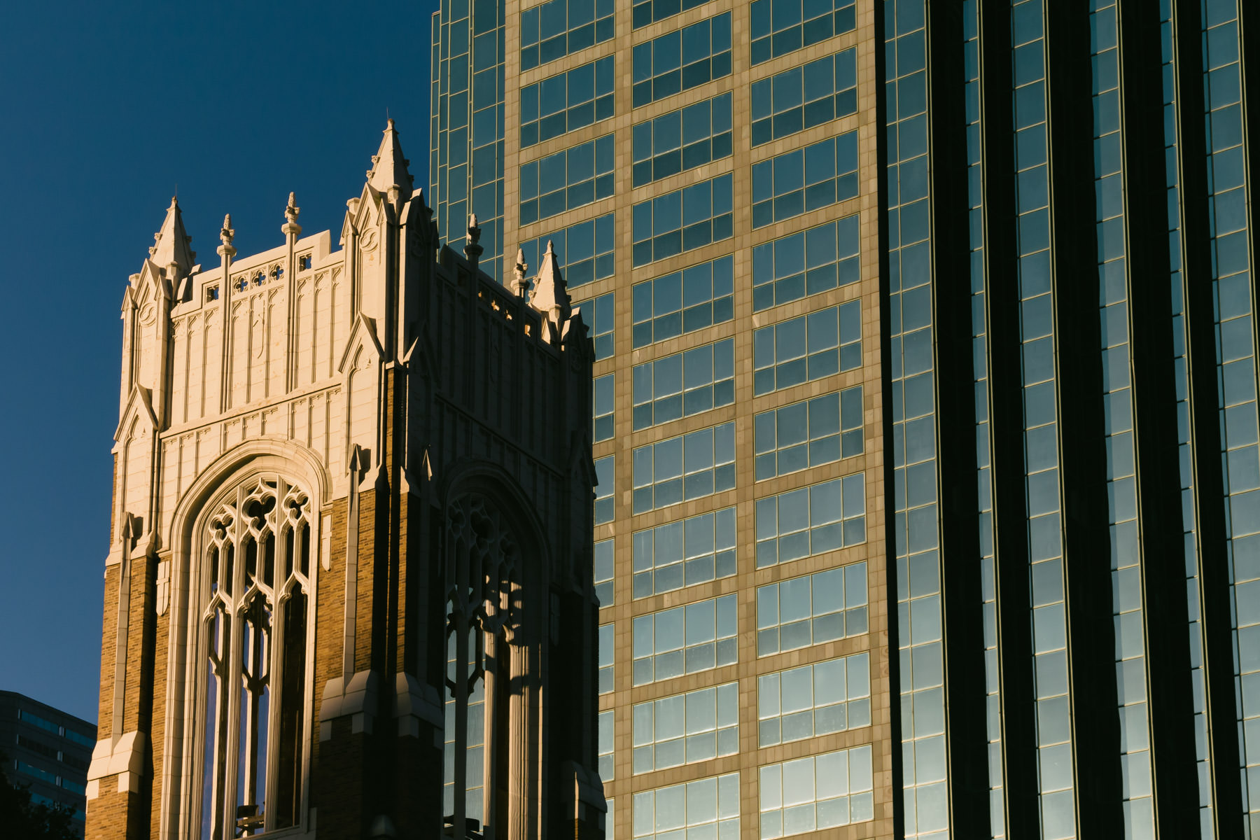 The bell tower of Dallas' First United Methodist Church rises to meet the morning sun amongst the skyscrapers of the city's downtown.