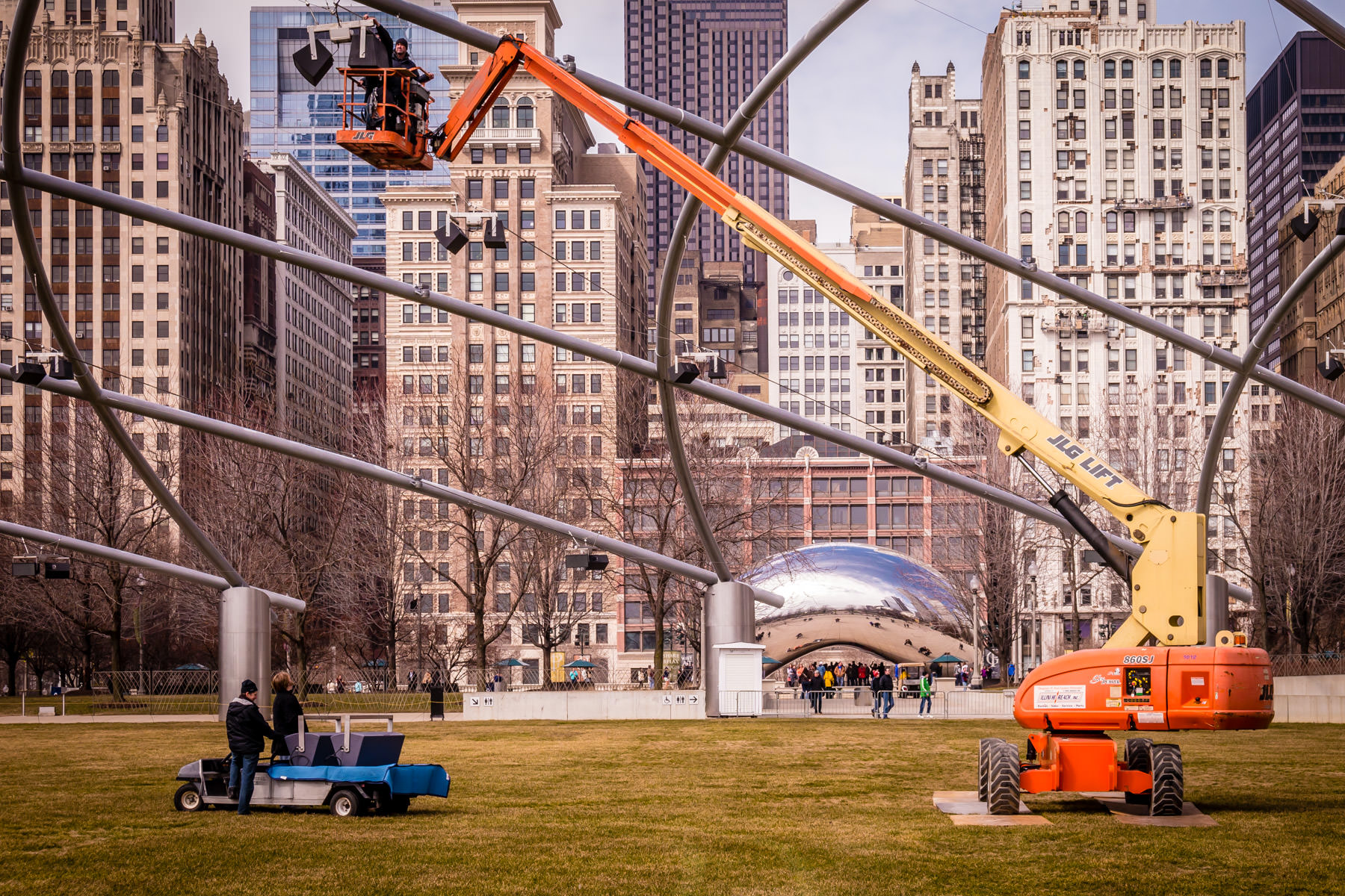 "Technicians work on a speaker hanging from the trellis of Chicago's Millennium Park's Jay Pritzker Pavilion as Anish Kapoor's ""Cloud Gate"" reflects its environment in the background."