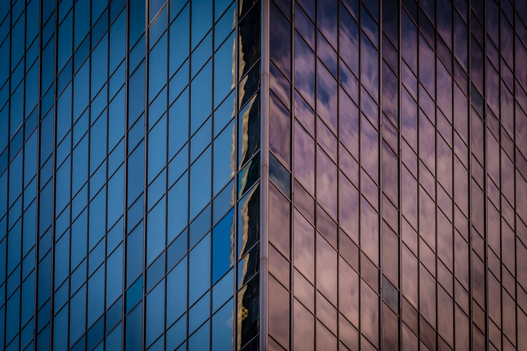 An abstract view of an exterior edge of Downtown Dallas' Renaissance Tower as its mirrored windows catch the early morning sun.