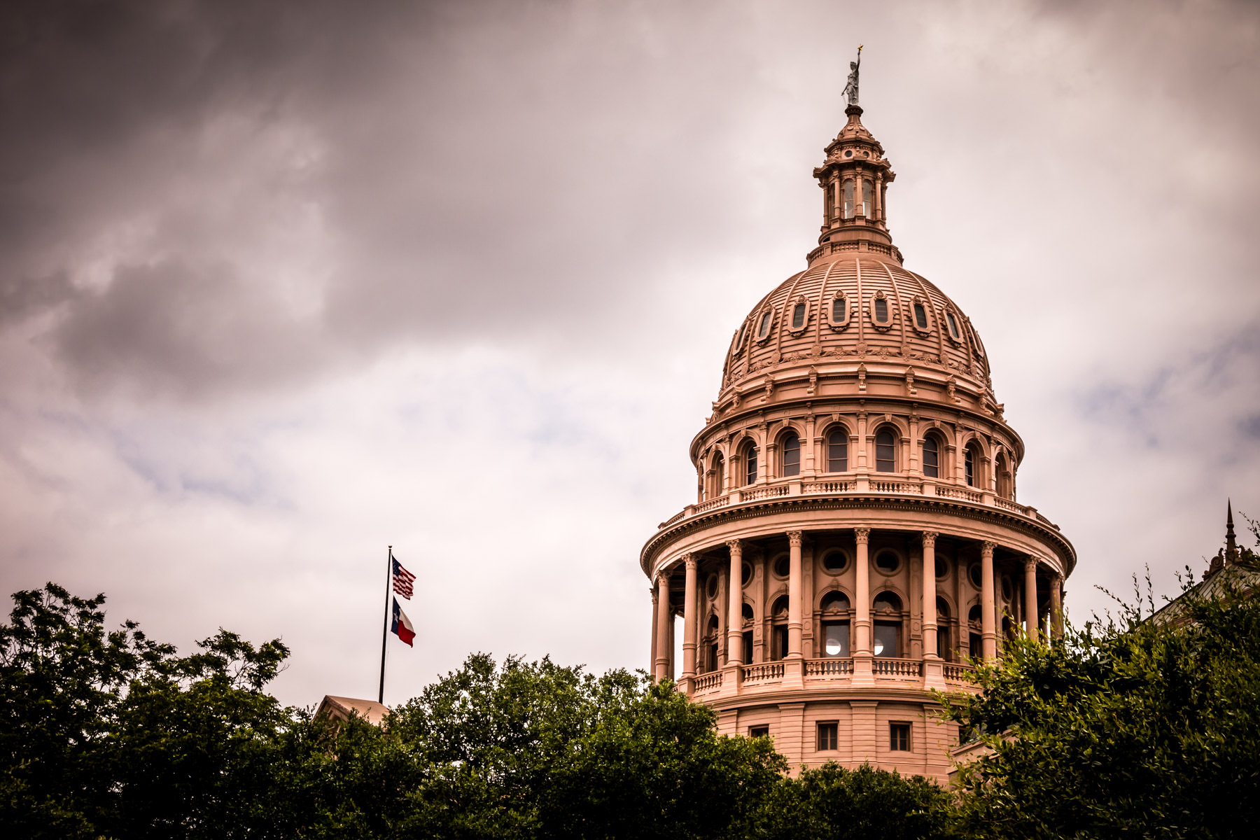 The rotunda and dome of the Texas State Capitol rises above the surrounding trees into the stormy skies over Austin.