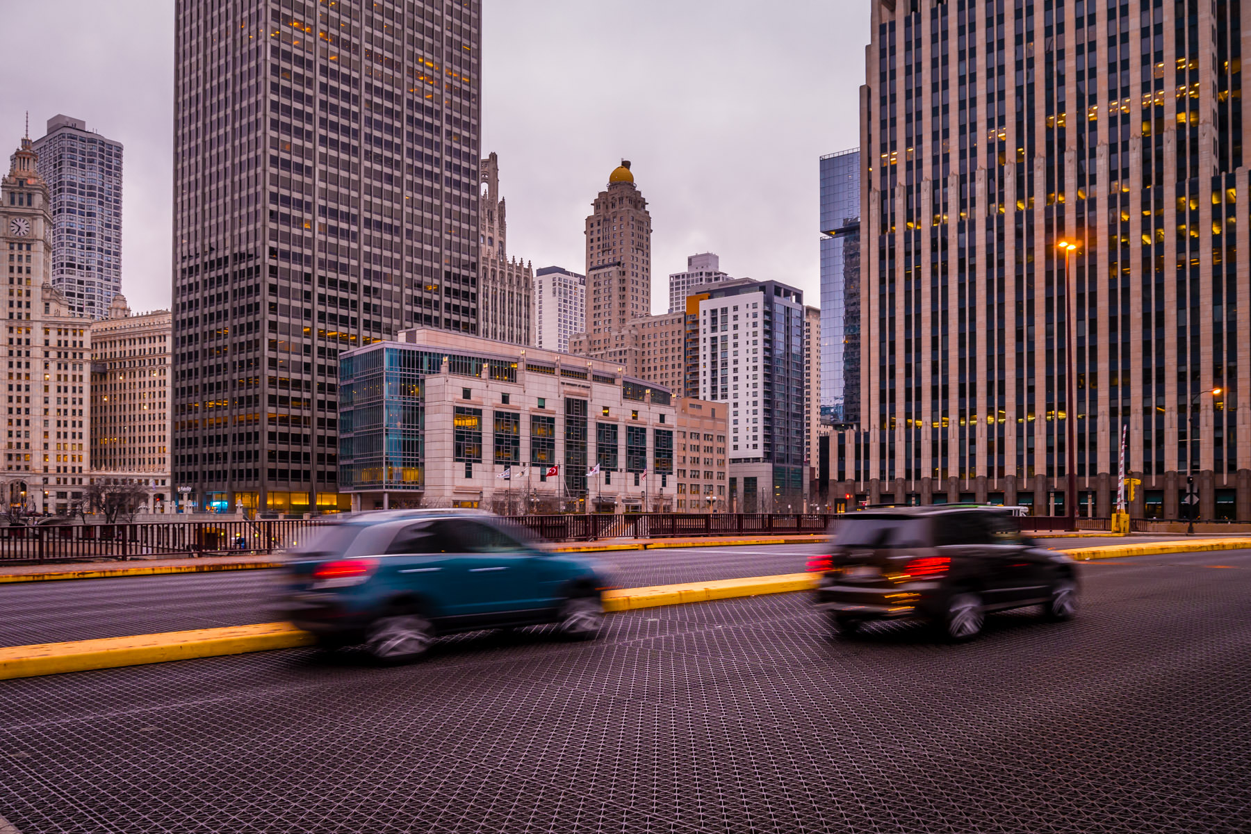Cars cross Chicago's Columbus Drive bridge as the city rises in the background on a cold, late-winter evening.